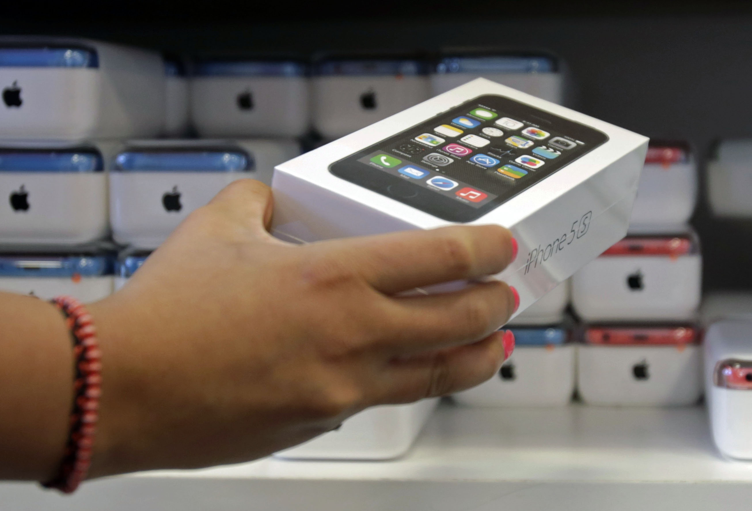 FILE – In this Friday, Sept. 20, 2013, file photo, a sales person pulls out an iPhone 5s for a customer during the opening day of sales of the iPhone 5s and iPhone 5C, in Hialeah, Fla. Apple says Monday, Sept. 23, 2013, that shoppers snapped up 9 million of its newest iPhones since the devices were launched Friday, and that demand is exceeding supply.  (AP Photo/Alan Diaz)