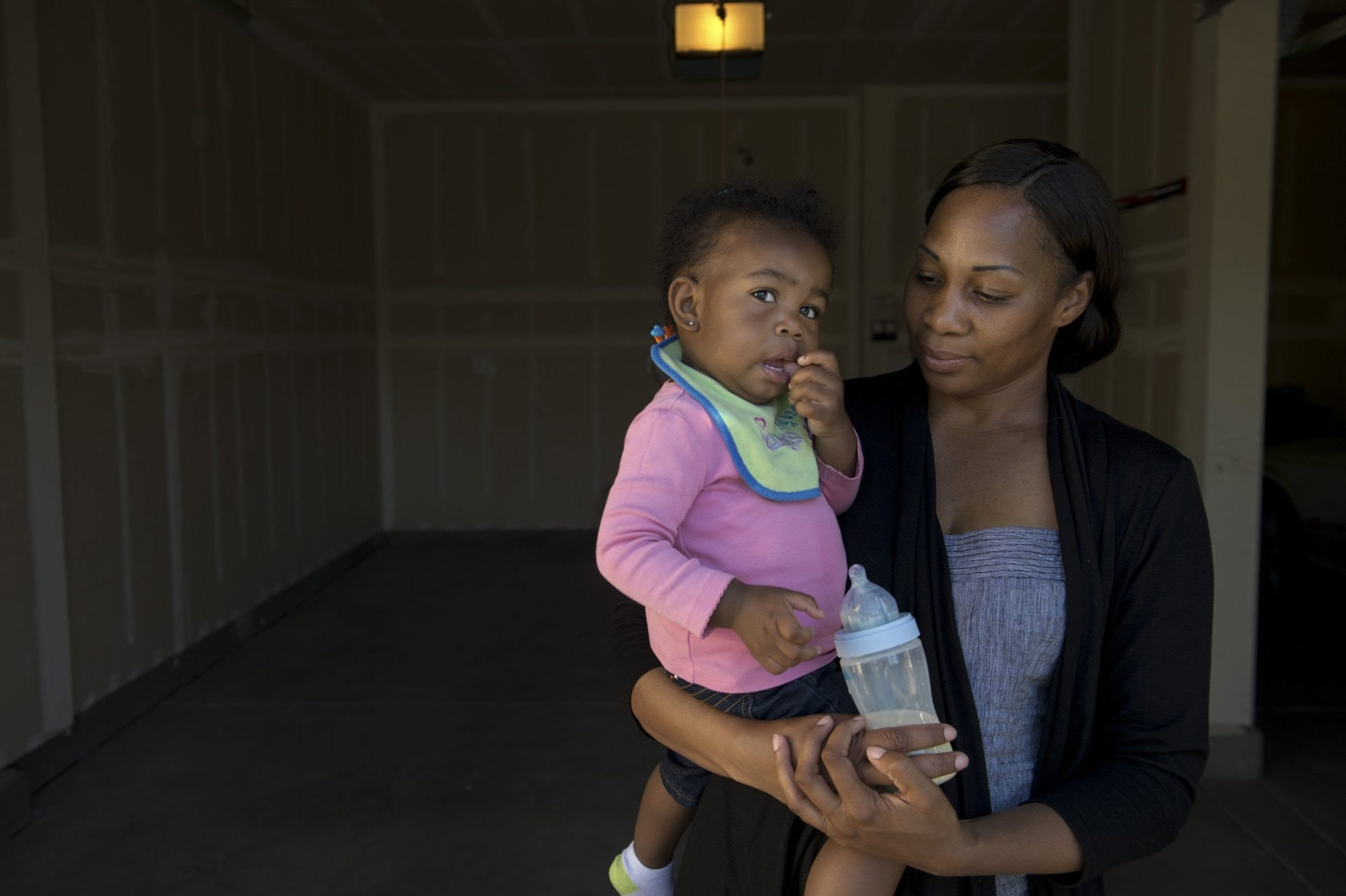 Shanell White, a single mother with her 14-month-old daughter, Imani Ross, is faced with an empty garage at her home in Elk Grove, Calif. She is a plaintiff in a class-action lawsuit against auto-title lenders.