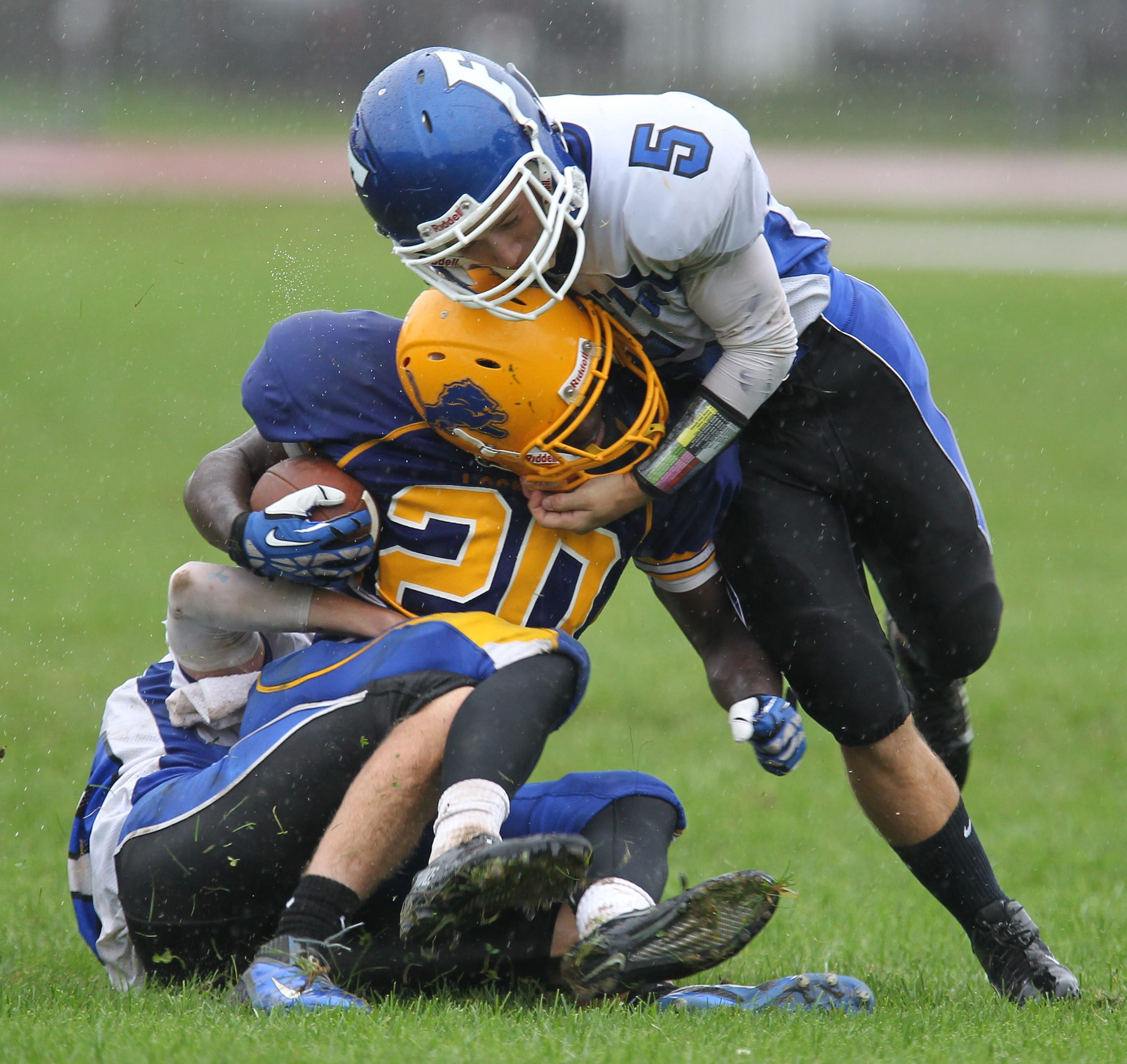 Frontier senior Rocco Russo, bottom, and junior Vinny Pupo, right, tackle Lockport junior running back Nick Hamilton on what was a great day for the Falcons' defense.