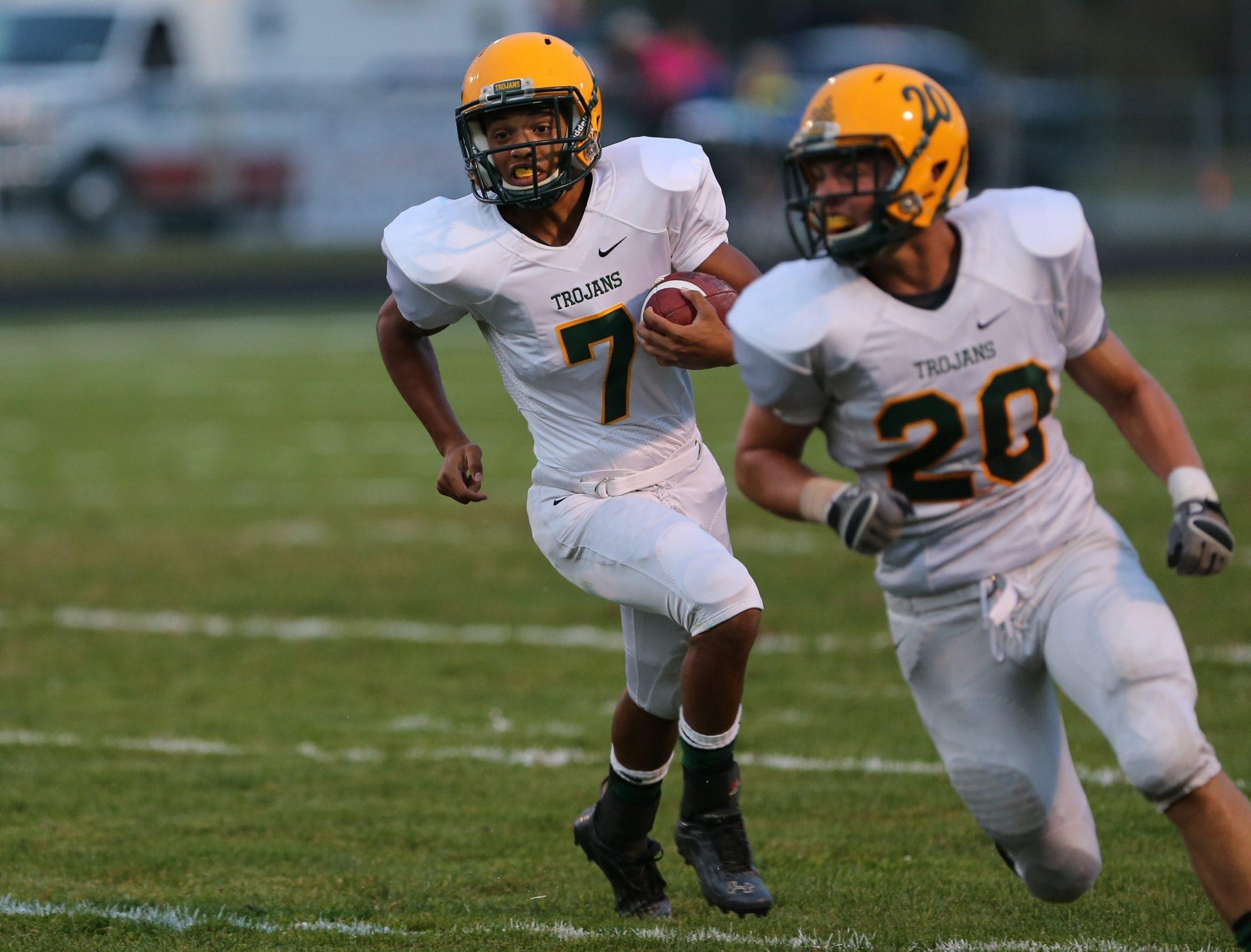 West Seneca East's Jolexis Santiago, left, runs for one of his two touchdowns against Iroquois.