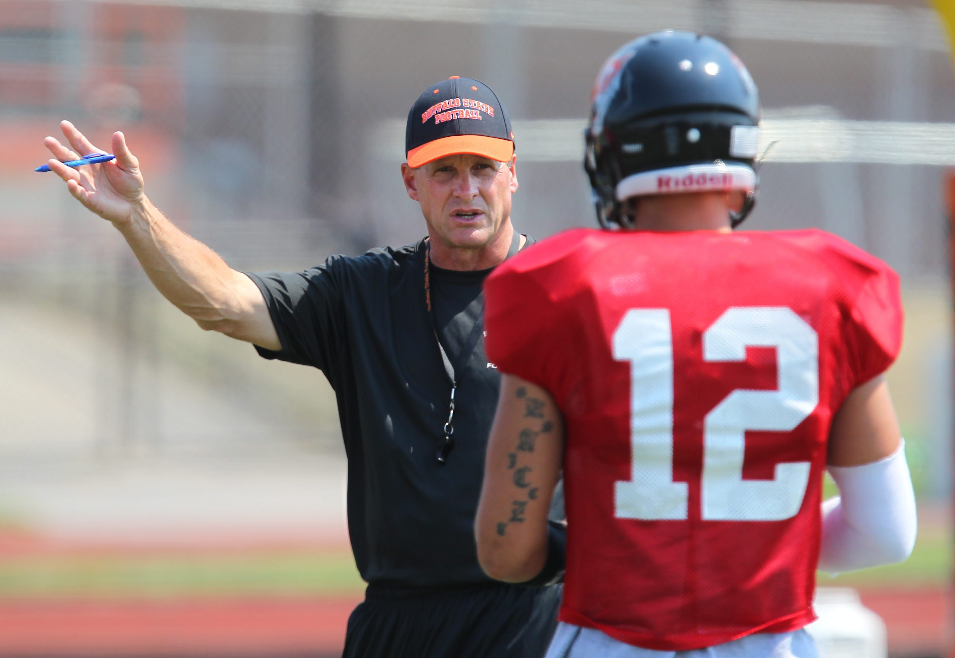 Buffalo State coach Jerry Boyes works with quarterback Casey Kacz during a recent practice.
