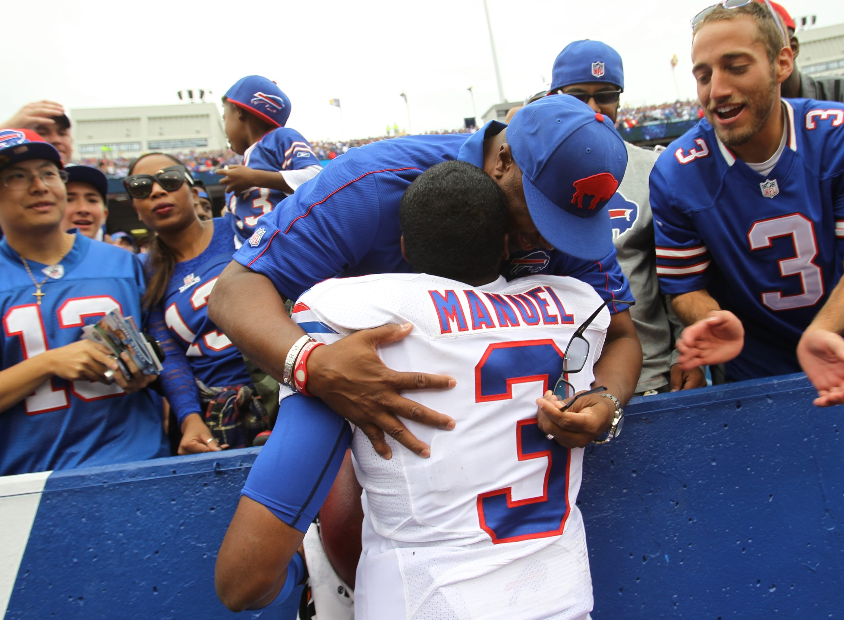 Buffalo Bills quarterback EJ Manuel (3) gives hugs to his dad, Erik Sr., after beating the Carolina Panthers at the Ralph Wilson Stadium on Sunday.  {Photo by James P. McCoy / Buffalo News}