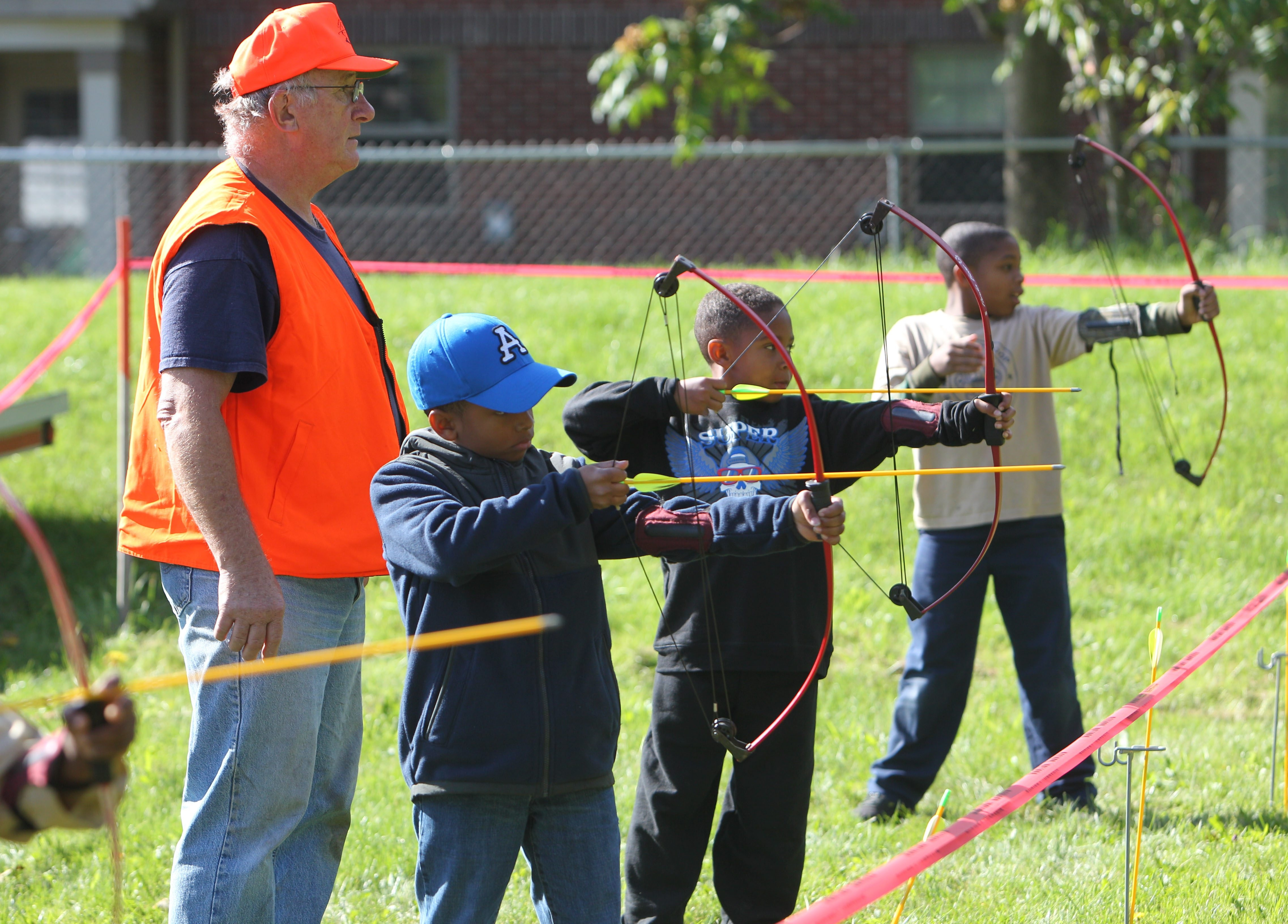 Mike Stewart teaches archery skills to Christopher Price, 10, Isaiah Allen, 8, and Keith Wilson, 9, at the fourth annual Buffalo District Camporee at St. Martin De Porres Church on Saturday.