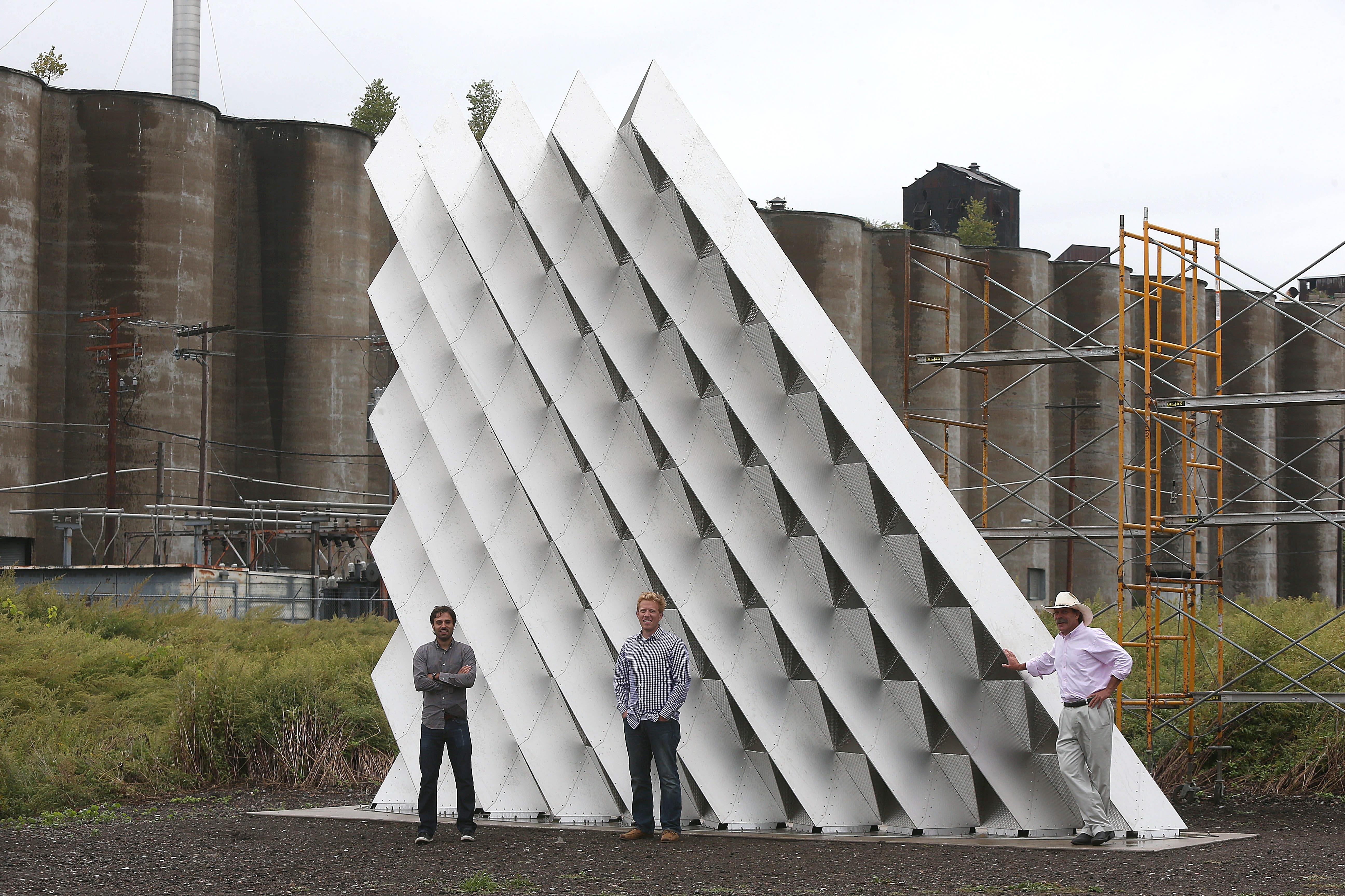 """With hat, Rick Smith, and UB architecture professors Chris Romano, center, and Nick Bruscia, in gray shirt, pose with the experimental facade """"Project 2XmT"""" near Childs St. in South Buffalo on Thursday, Sept. 12, 2013.  (Robert Kirkham/Buffalo News)"""