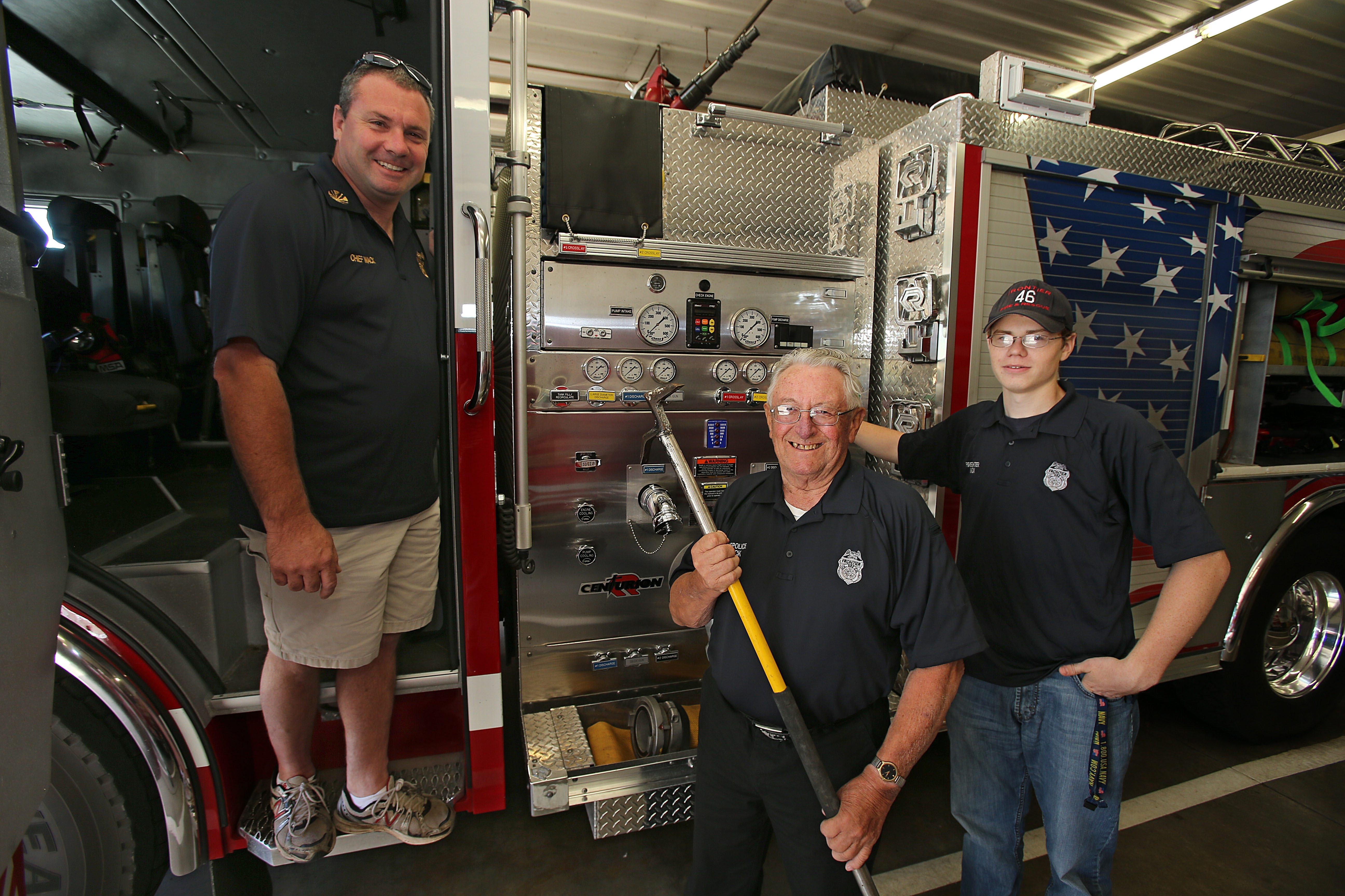 Spirit of Frontier Volunteer Fire Department is embodied by Mack family – from left, Fire Chief Bruce, 43; his dad, Harvey Jr., 79; and Bruce's son, Brandon, 18 – serving together at station in Wheatfield. The late Harvey Mack Sr. was a charter member in 1939.