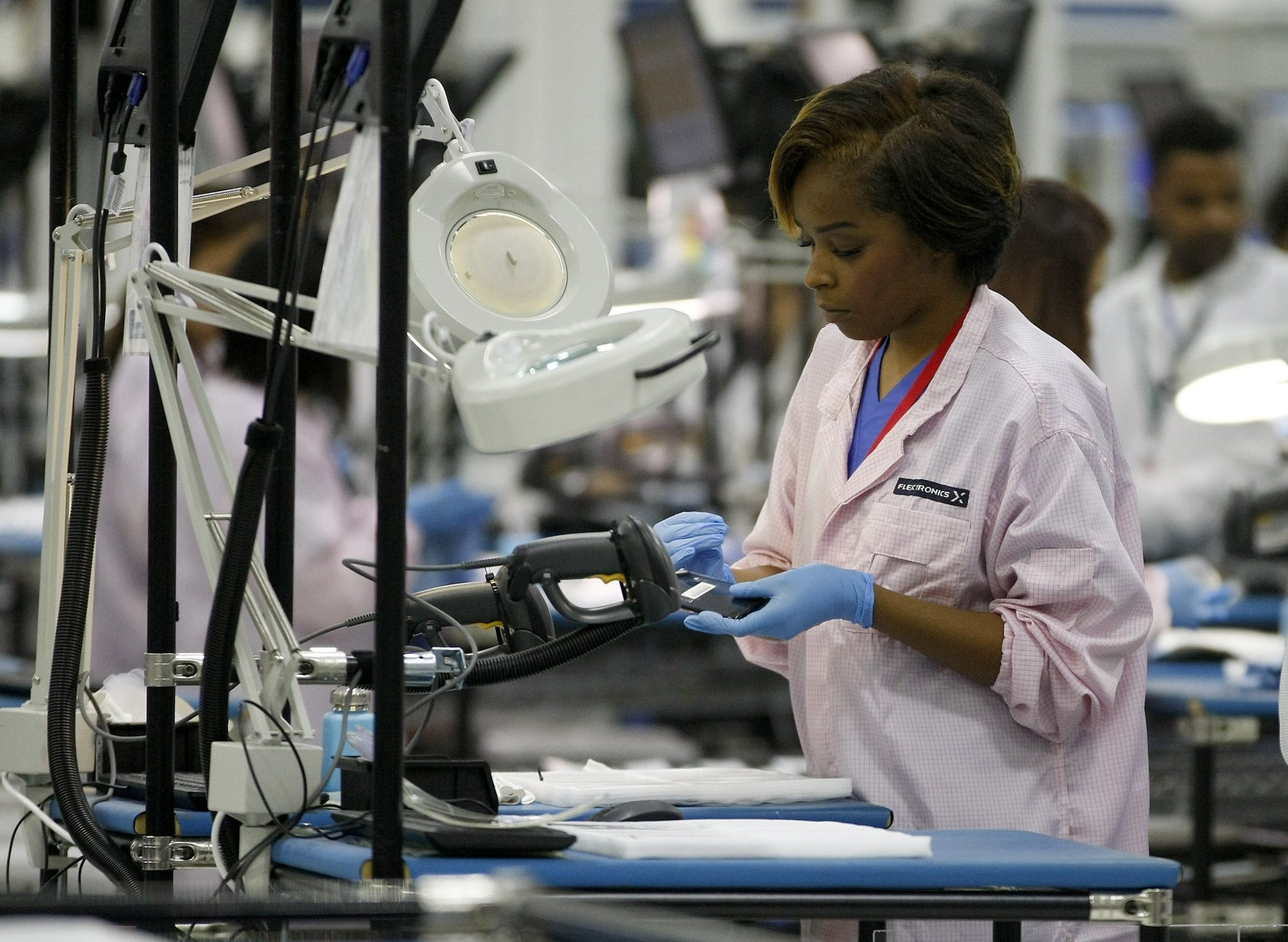 A Moto X phone goes through quality control at Flextronics, a plant making the new phones in Fort Worth, Texas. Google Inc. Chairman Eric Schmidt called the opening of the plant a step toward changing the perception of manufacturing in the U.S.