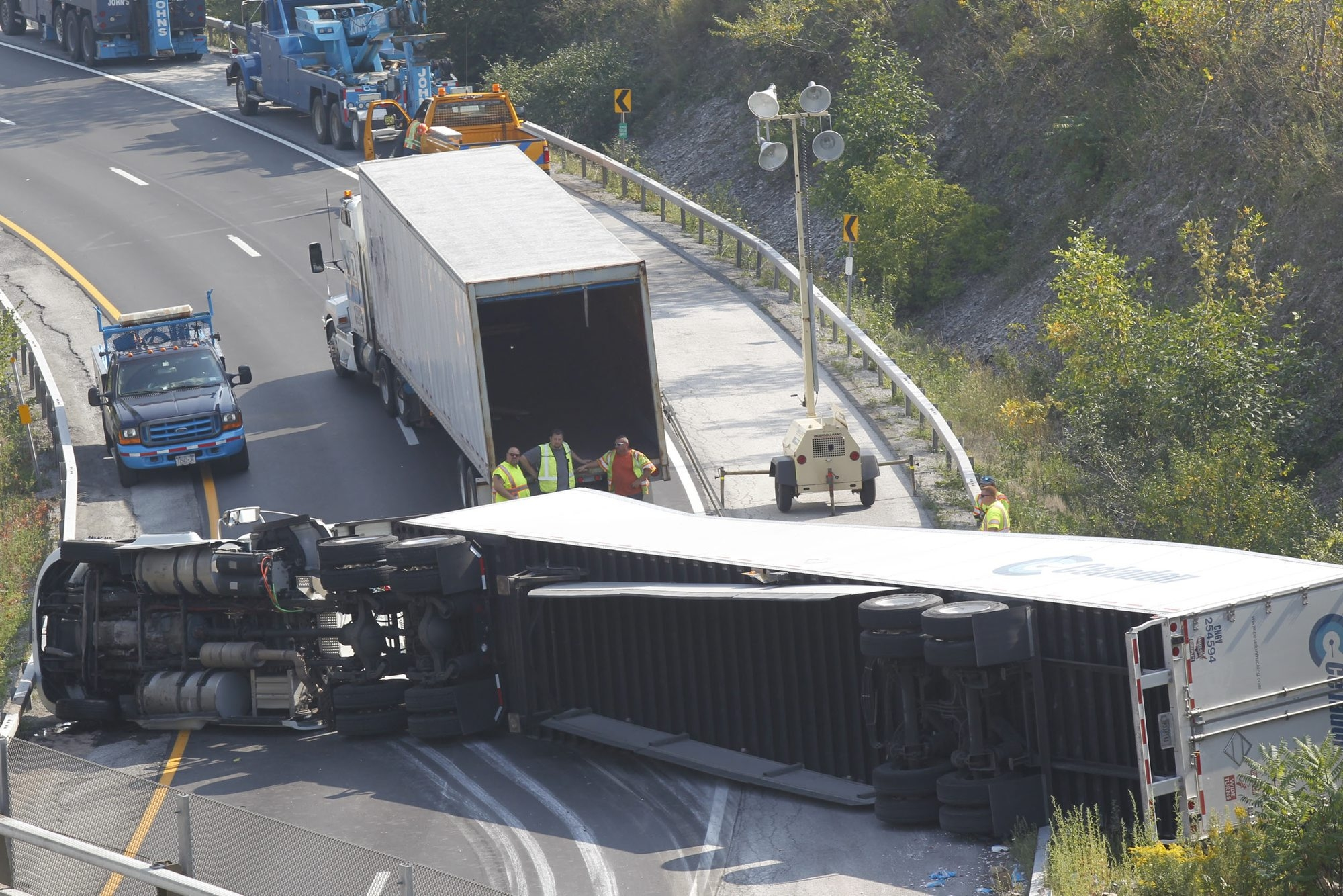 The driver of the tractor-trailer lost control, overturning the truck and spilling his cargo onto the roadway.