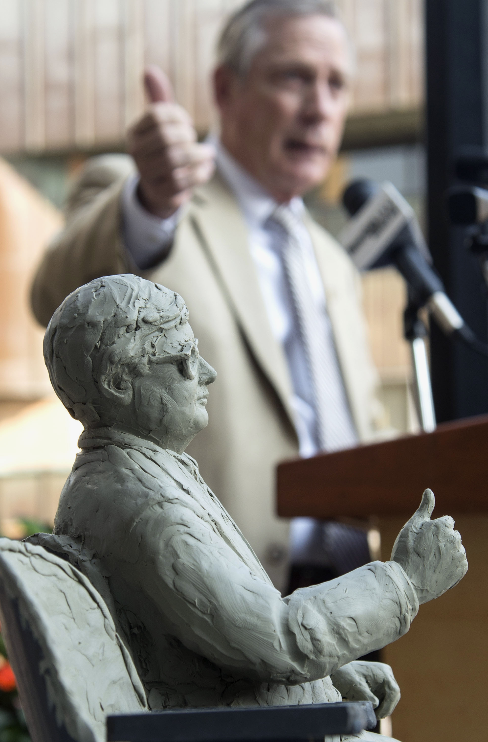 Scott Anderson gives a thumbs up next a scale model of a sculpture of famed film critic Roger Ebert.