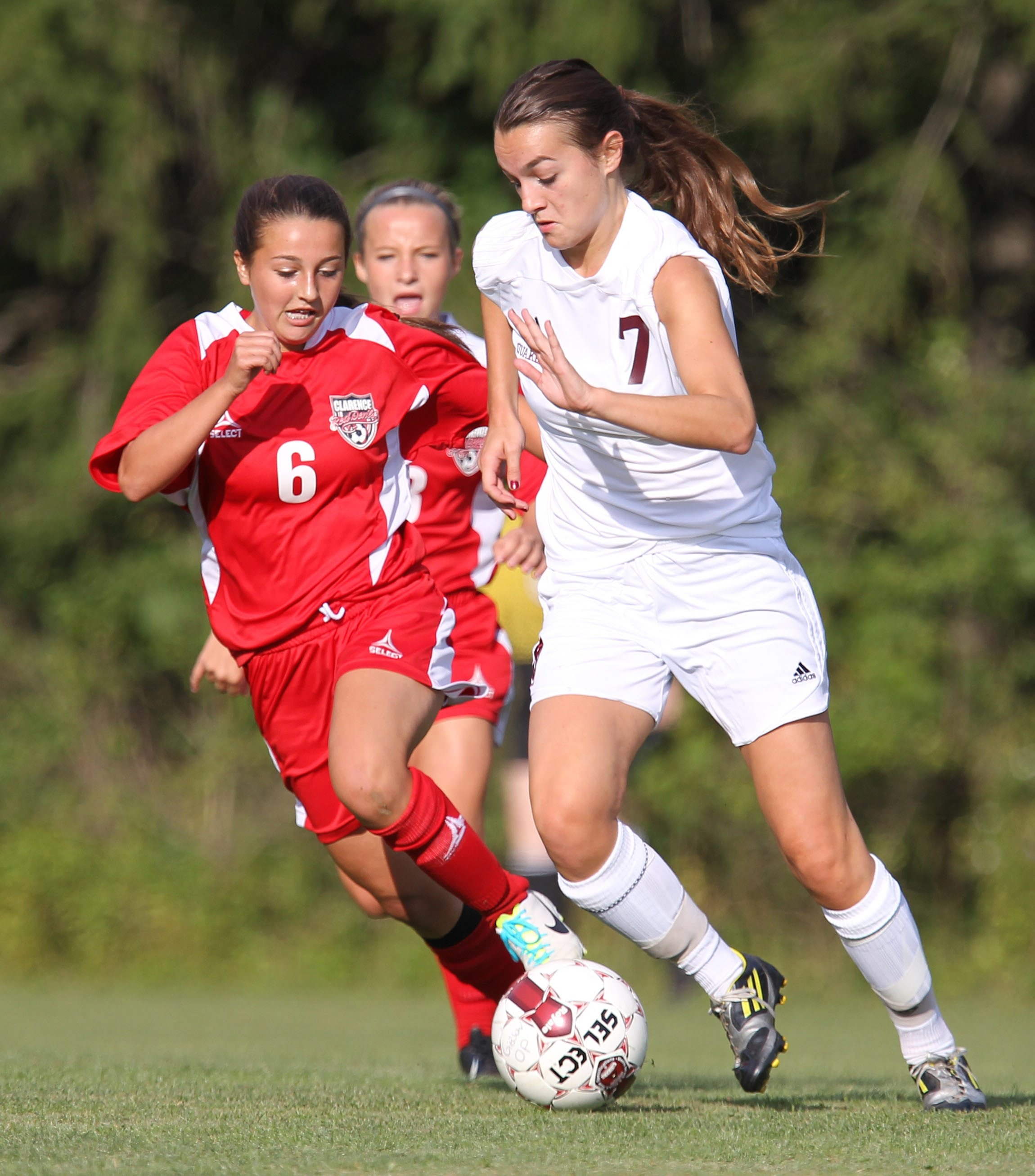 Orchard Park's Emma Saul (7) moves the ball past Clarence's Riley Bowers during the first half of their game at Orchard Park on Friday.