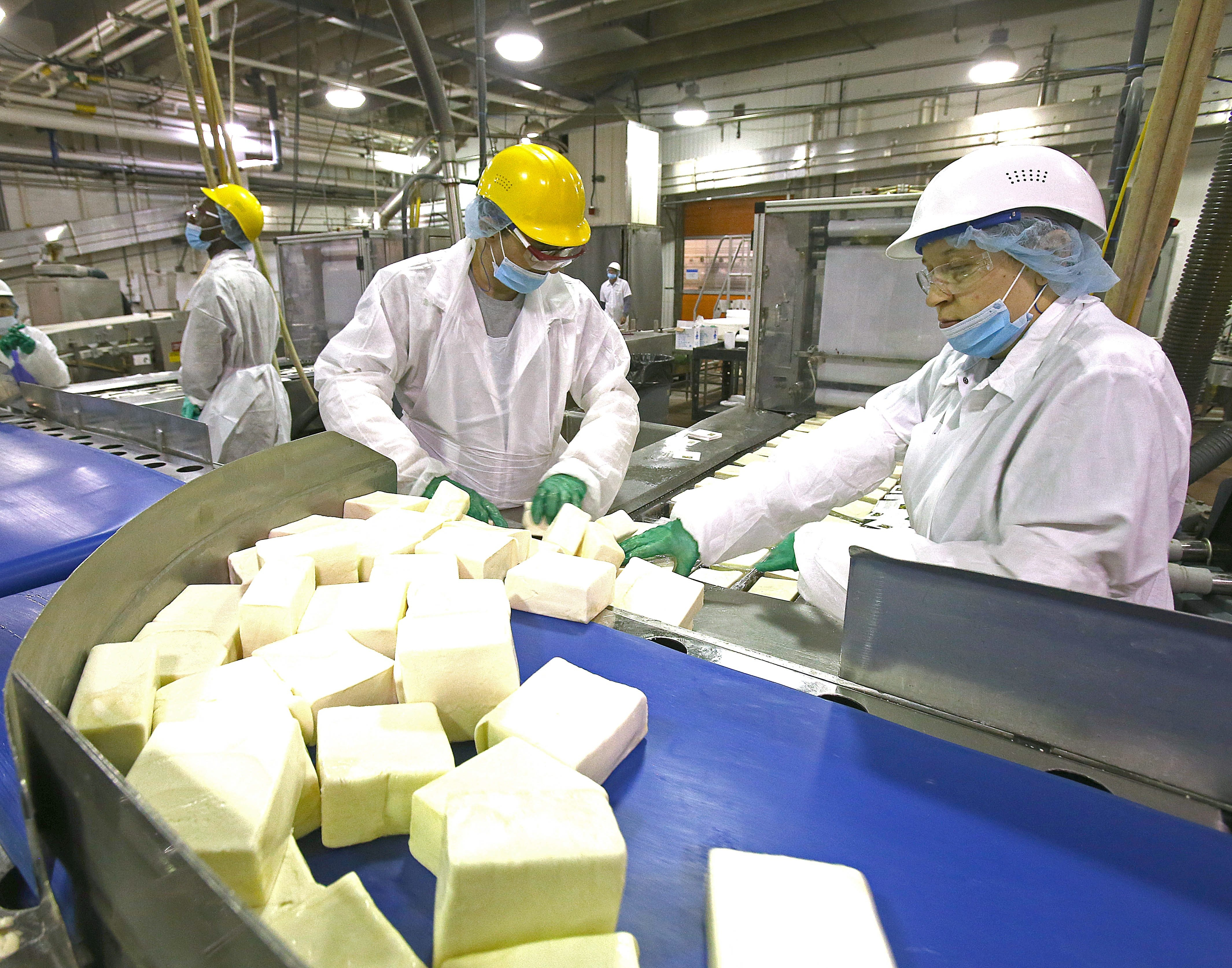 Sorrento employees Bruce Mucciaccio, left, and Kelly Chrisler will continue to process mozzarella  at the South Park Avenue plant.