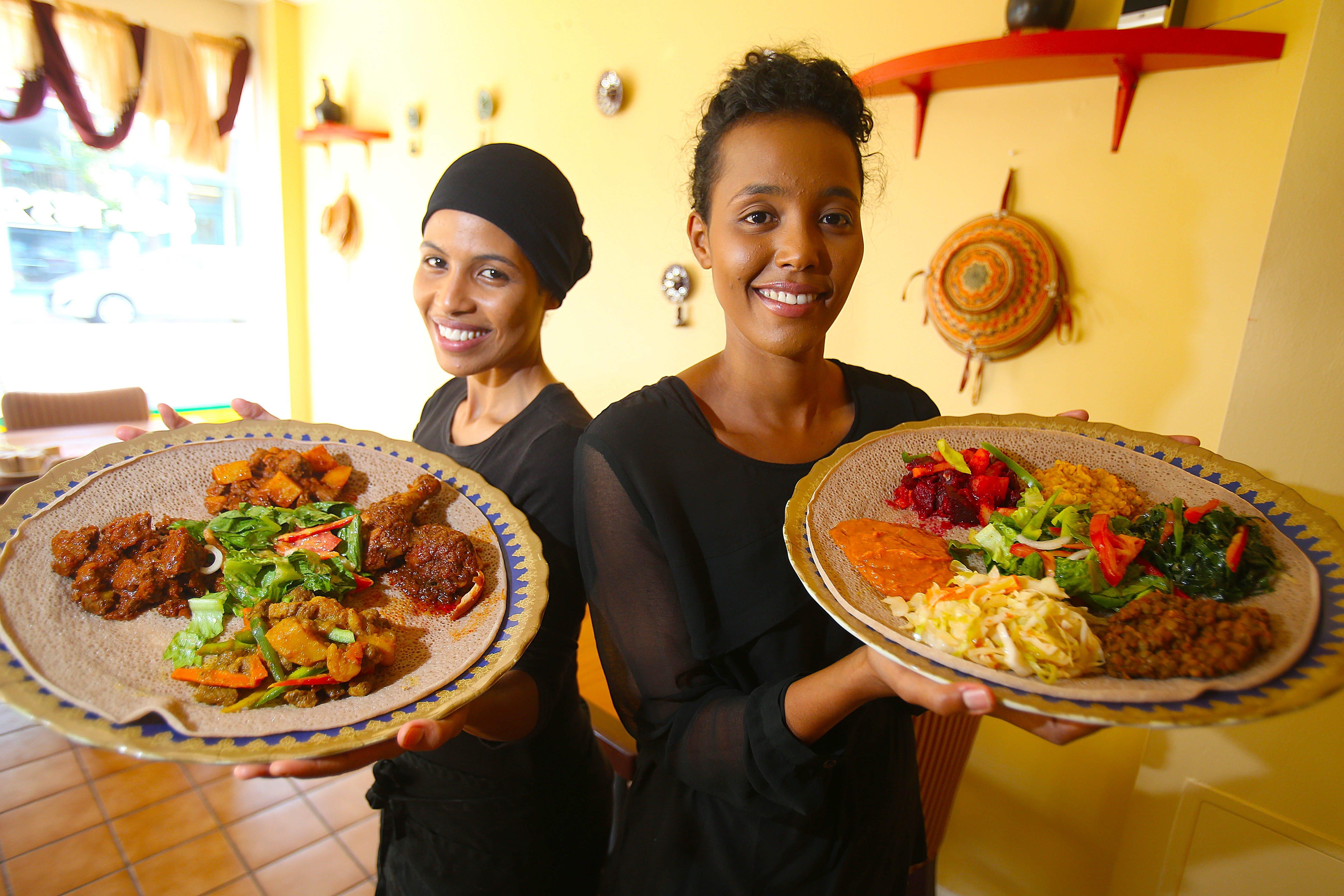 Owner Iman Gatur, left, shows off the Meat Combo and her sister Sabat Gatur holds the Veggie Combo at Gatur's Ethiopian Restaurant on Allen Street. (Robert Kirkham/Buffalo News)