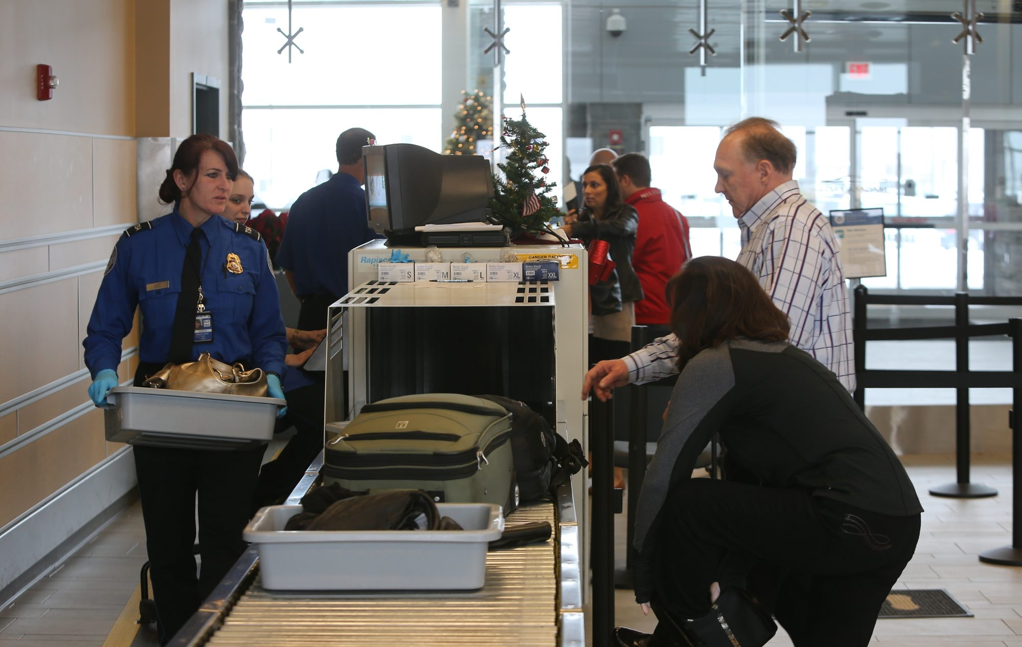 Transportation Security Administration officials carry plastic trays as passengers watch their belongings go through the scanner at the security check at Niagara Falls International Airport.