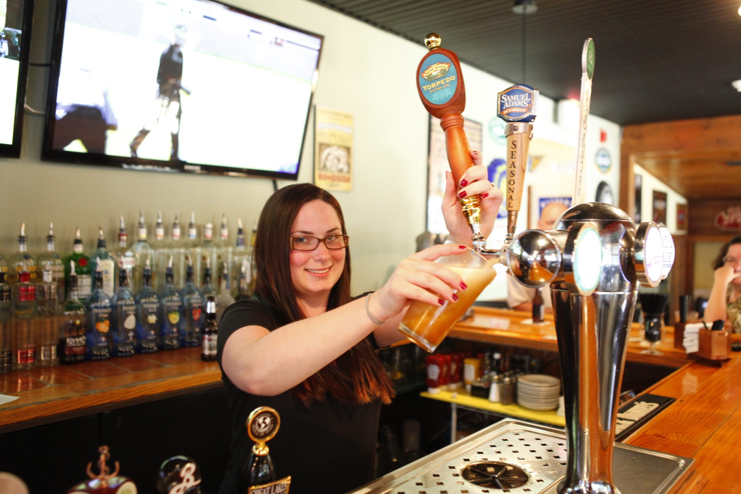Danielle Allein pours a draft beer at the Ebenezer Ale House. There are more than 80 different types available.