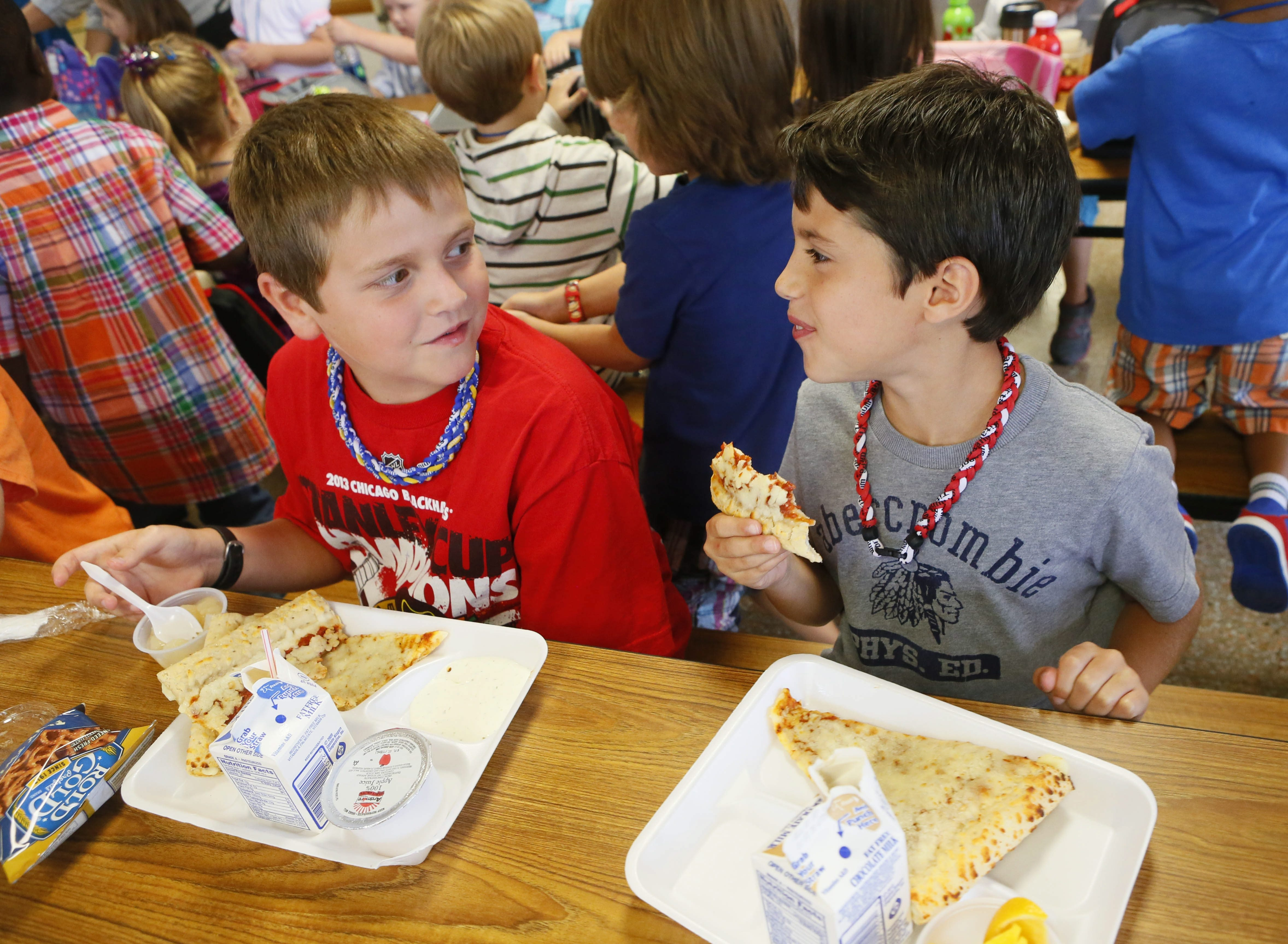 Fourth-graders Ben Balazs, left, and Caden Cavalieri seem to be enjoying their lunches on the first day of school at Maple East Elementary School in the Williamsville district Tuesday.
