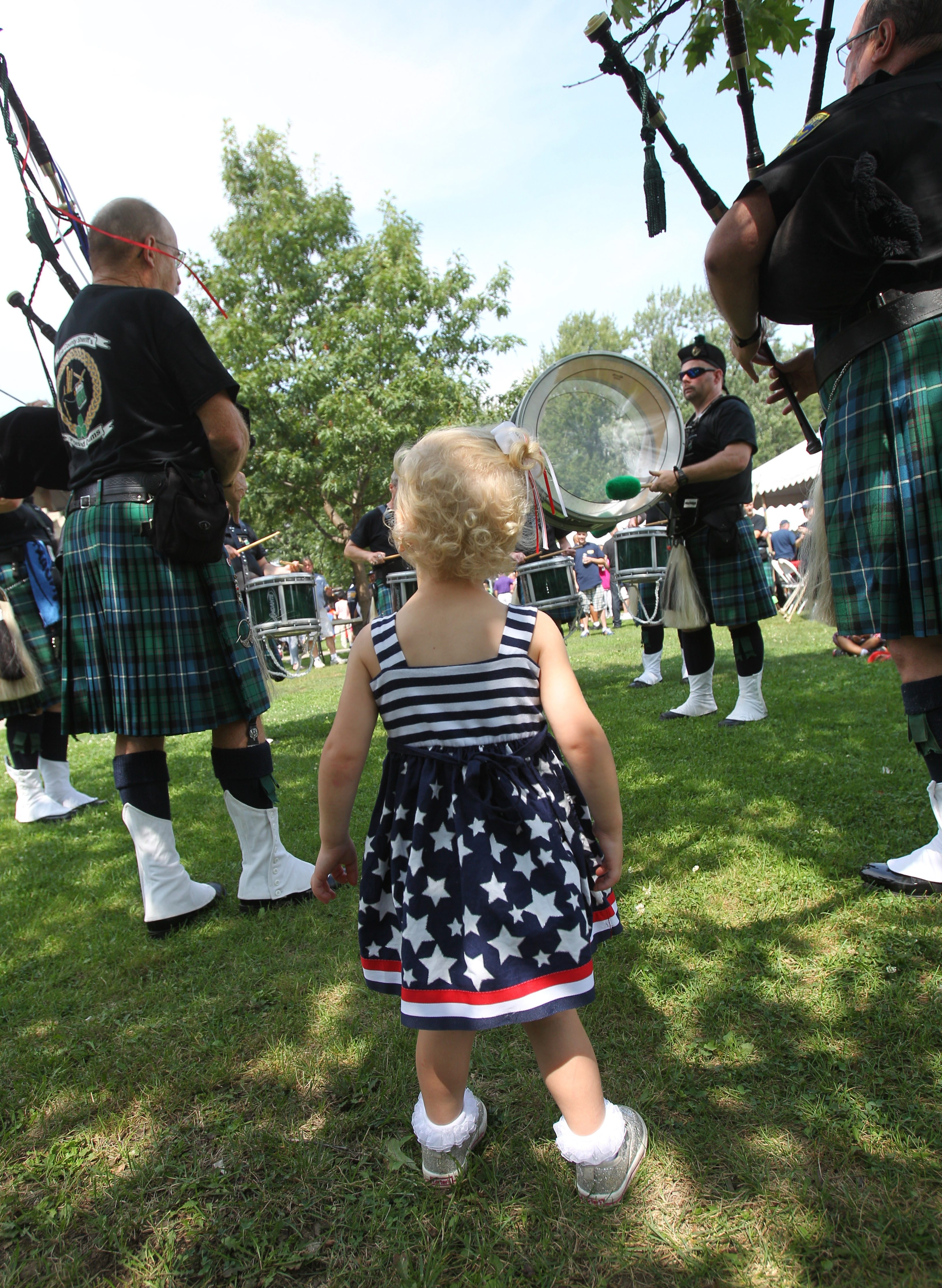 Felicity Keough, 2, of South Buffalo, dances to the music of the Sheriff's Pipes and Drums after marching in the parade with her family.