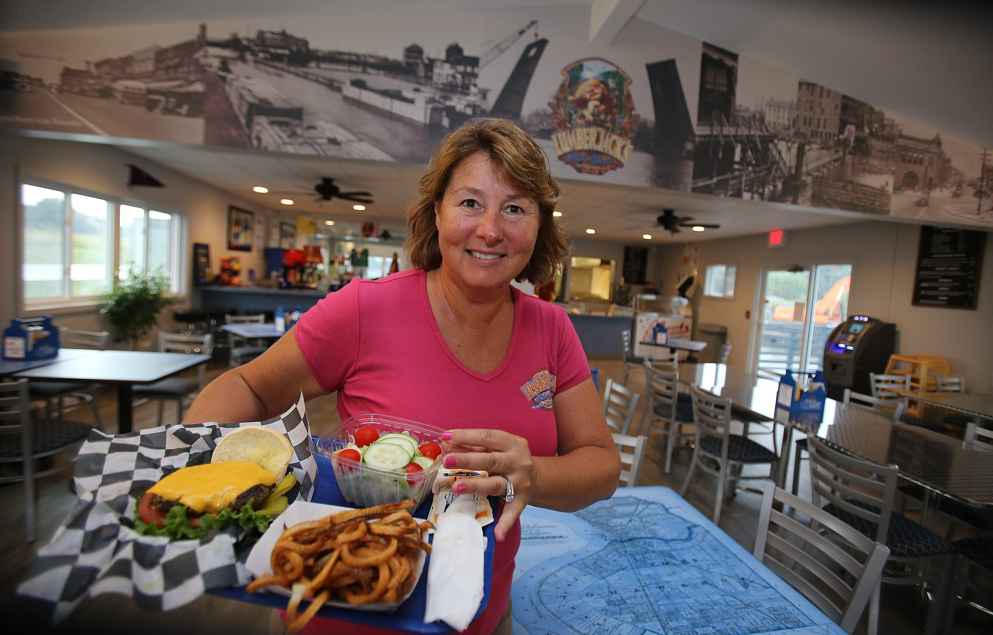 Manager Mary Lou Pieper shows off cheeseburger platter with fresh-cut curly-Q fries at Lumberjack's Patio Grill on the shores of the Niagara River in North Tonawanda.