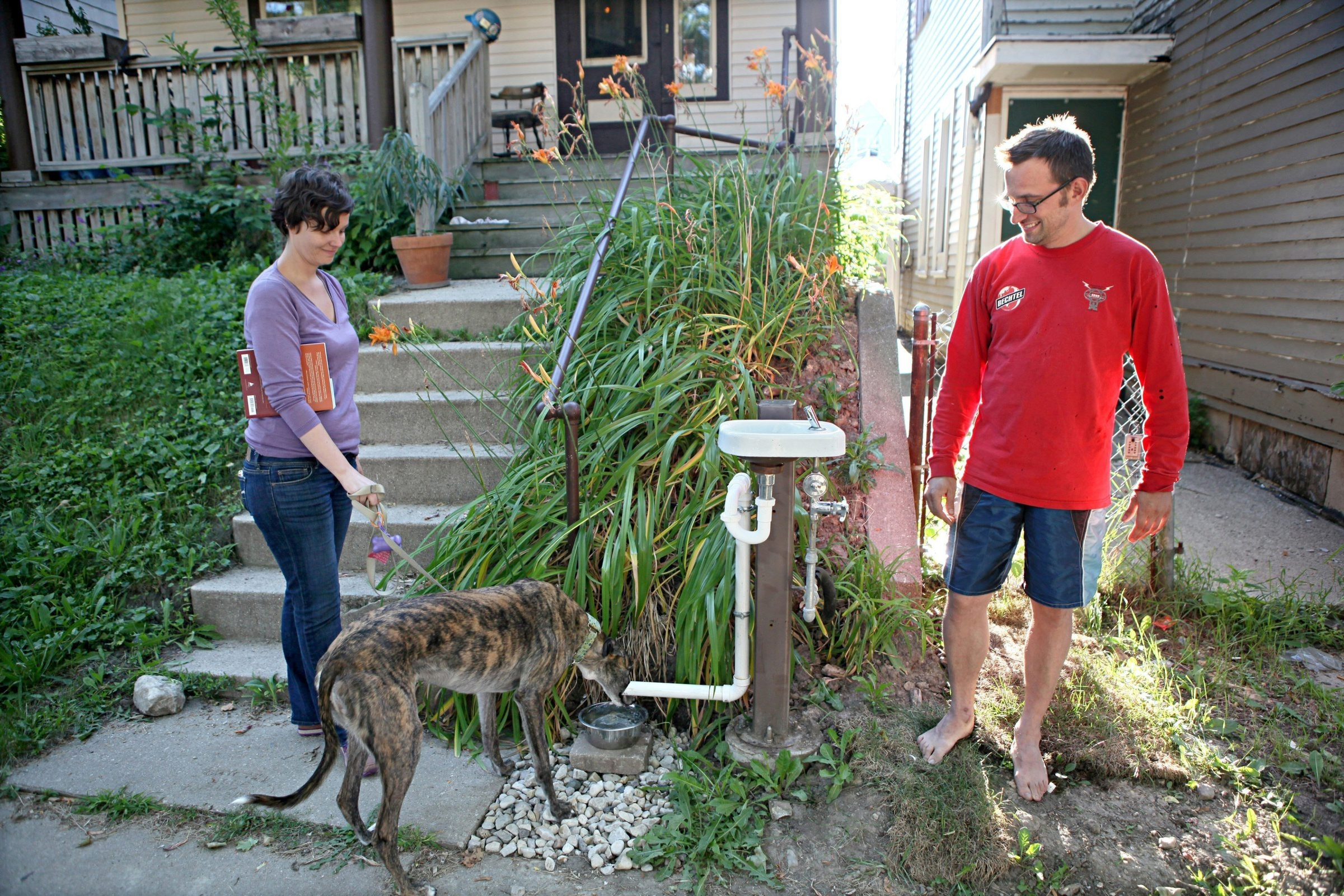 Jessica Burch stops to let her dog have a drink from the doggy dish as they walk past Micah MacArthur's house. MacArthur, right, installed the bubbler that he built in front of his house for public use in Milwaukee's Riverwest neighborhood.