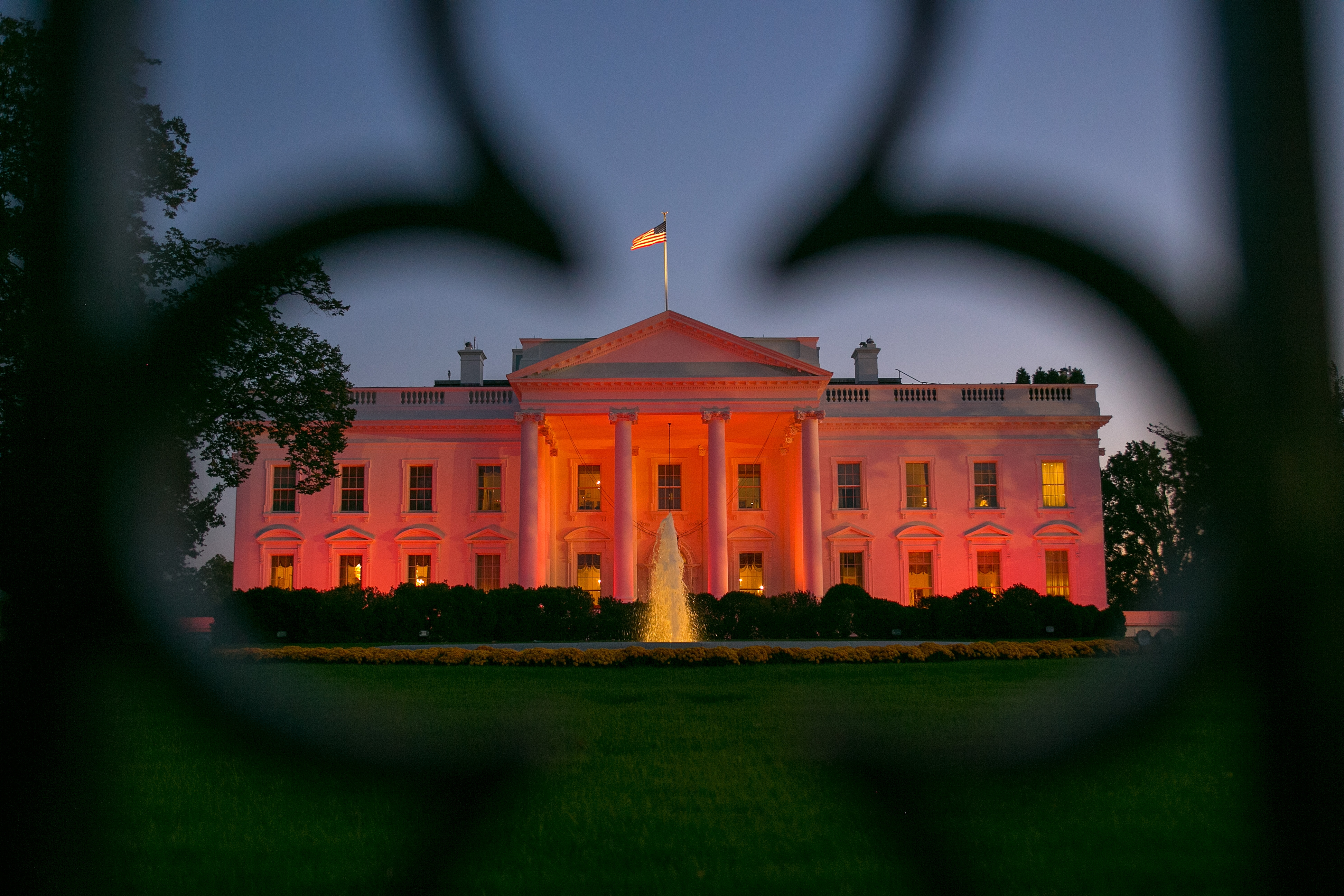 The White House, seen through its fence, is bathed in pink Thursday in honor of Breast Cancer Awareness Month.