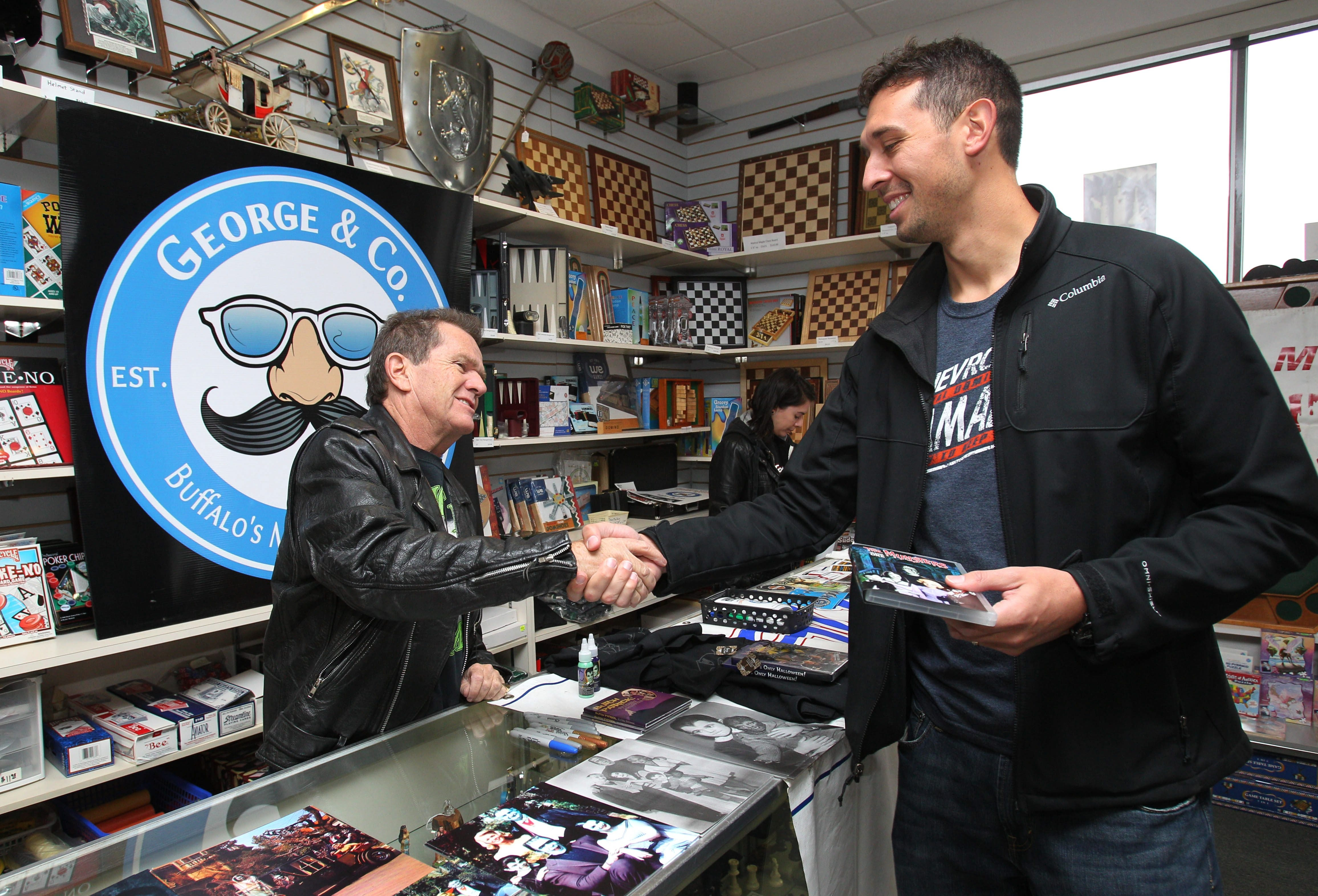 "Butch Patrick, left, who played Eddie Munster in the TV series ""The Munsters,"" talks Saturday with fan Eric Jankowski of Depew, who was first in line to see the former child actor at George & Co. in Amherst."