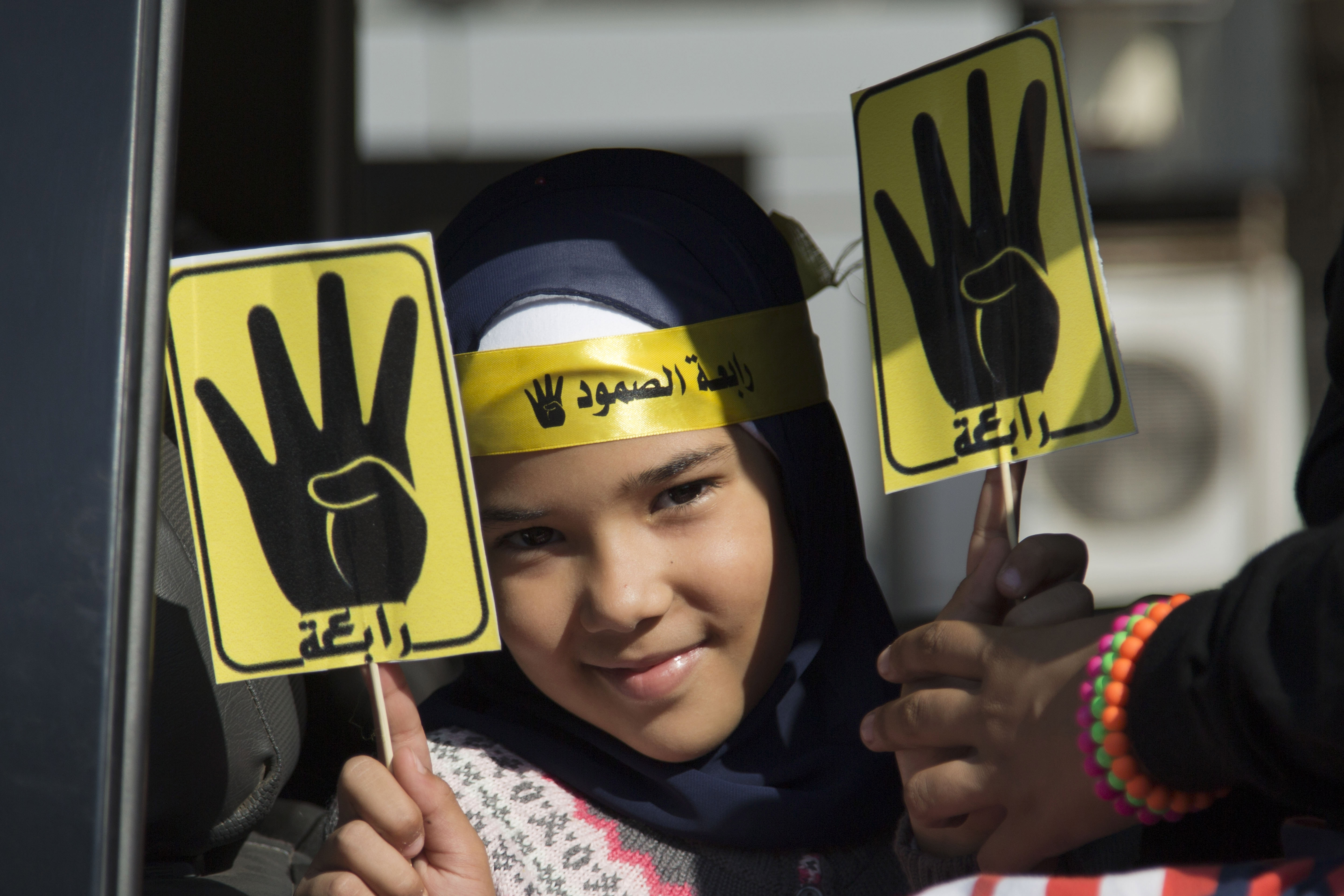 "A supporter of Egypt's ousted President Mohammed Morsi holds placards showing an open palm with four raised fingers, which has become a symbol of the Rabaah al-Adawiya mosque, where Morsi supporters had held a sit-in for weeks that was violently dispersed in August, during a protest in Cairo, Egypt, Friday, Oct. 11, 2013. Thousands of Morsi supporters took to the streets Friday in several cities, commemorating 100 days since Egypt's first democratically elected president was ousted by the military following mass protests calling for his resignation. The Arabic on the placard reads, ""Rabaah."" (AP Photo/Hassan Ammar)"