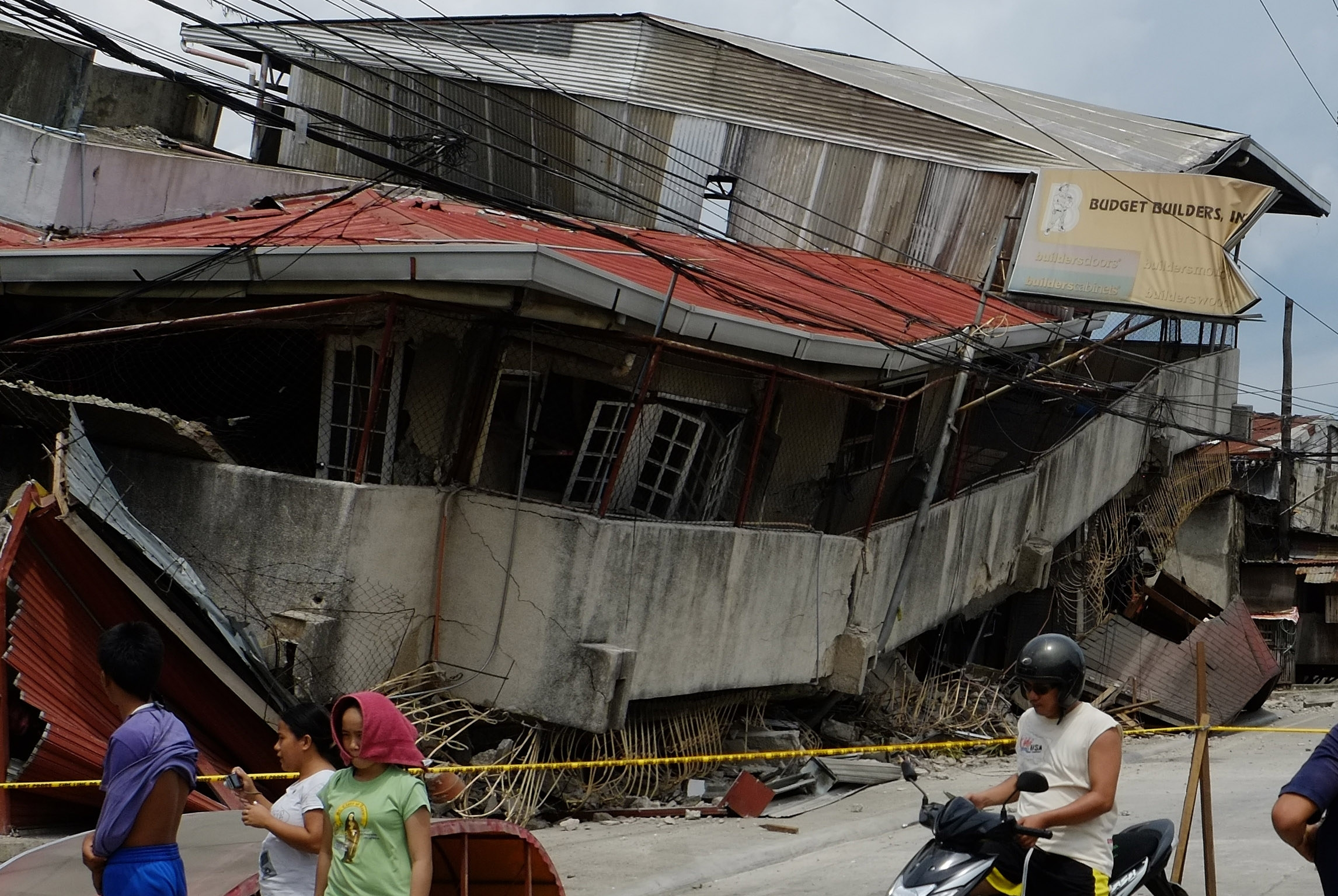 Residents walk past a damaged structure in Cebu, Philippines, Tuesday. A 7.2-magnitude earthquake struck in the central Philippines on Tuesday morning, killing at least 67 people and injuring hundreds.