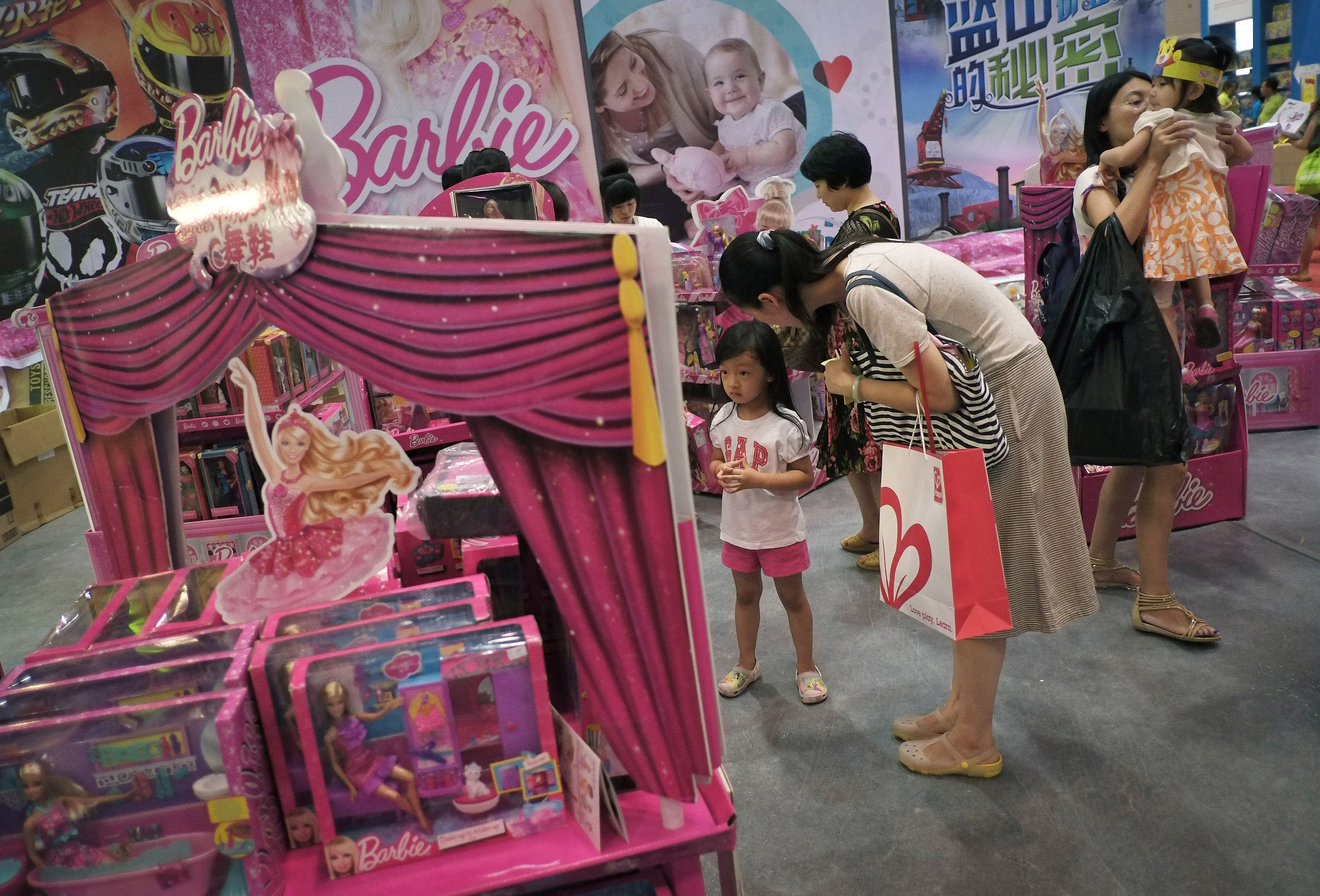 Mothers with their children eye Barbie toys for sale in Beijing in July. Barbie doll sales reversed four straight quarters of decline to increase 3 percent during the third quarter.