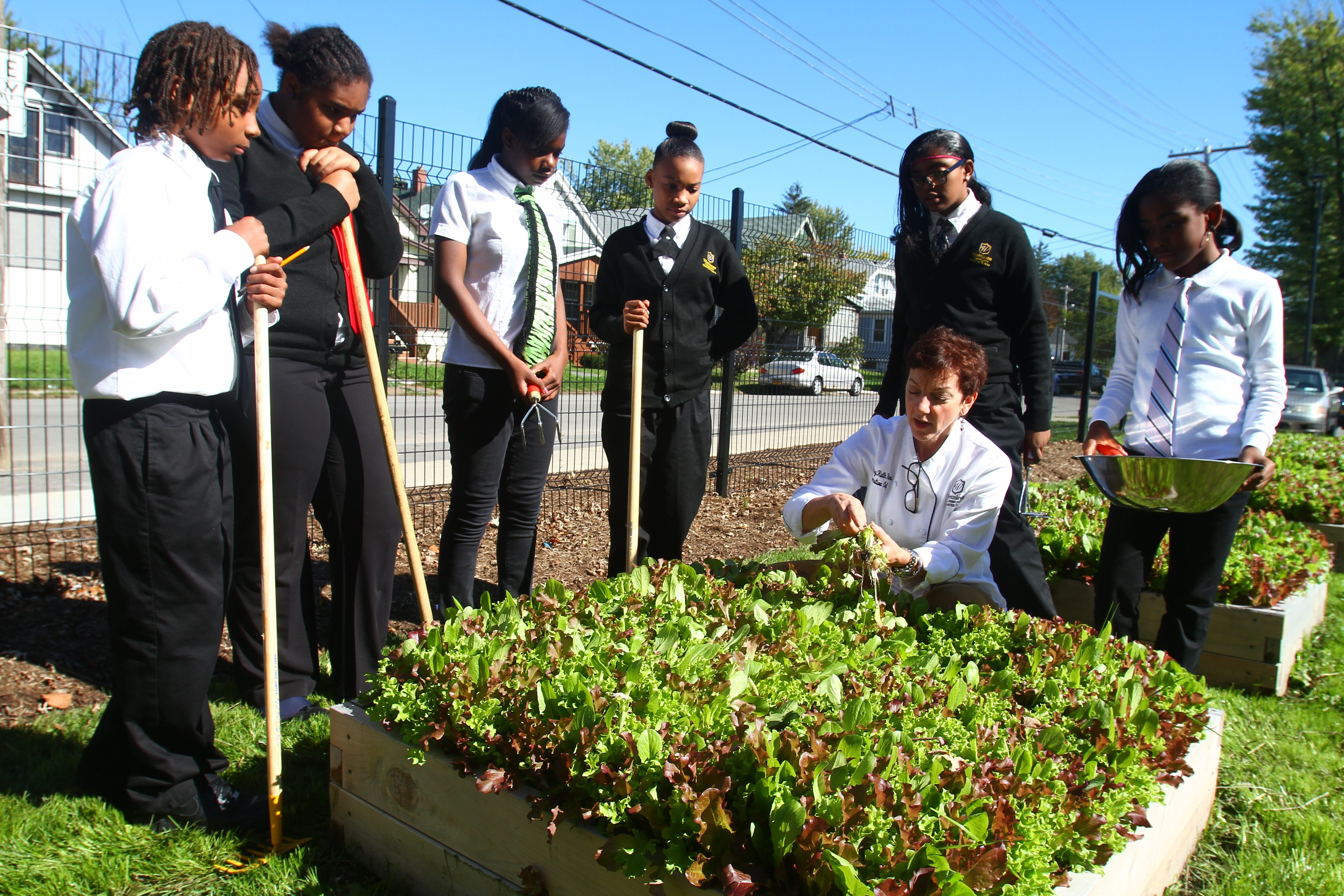 Chef MaryRuth Rera shows students how to select greens in the garden at Westminster Community Charter School. Rera routinely does classroom tastings at Westminster.