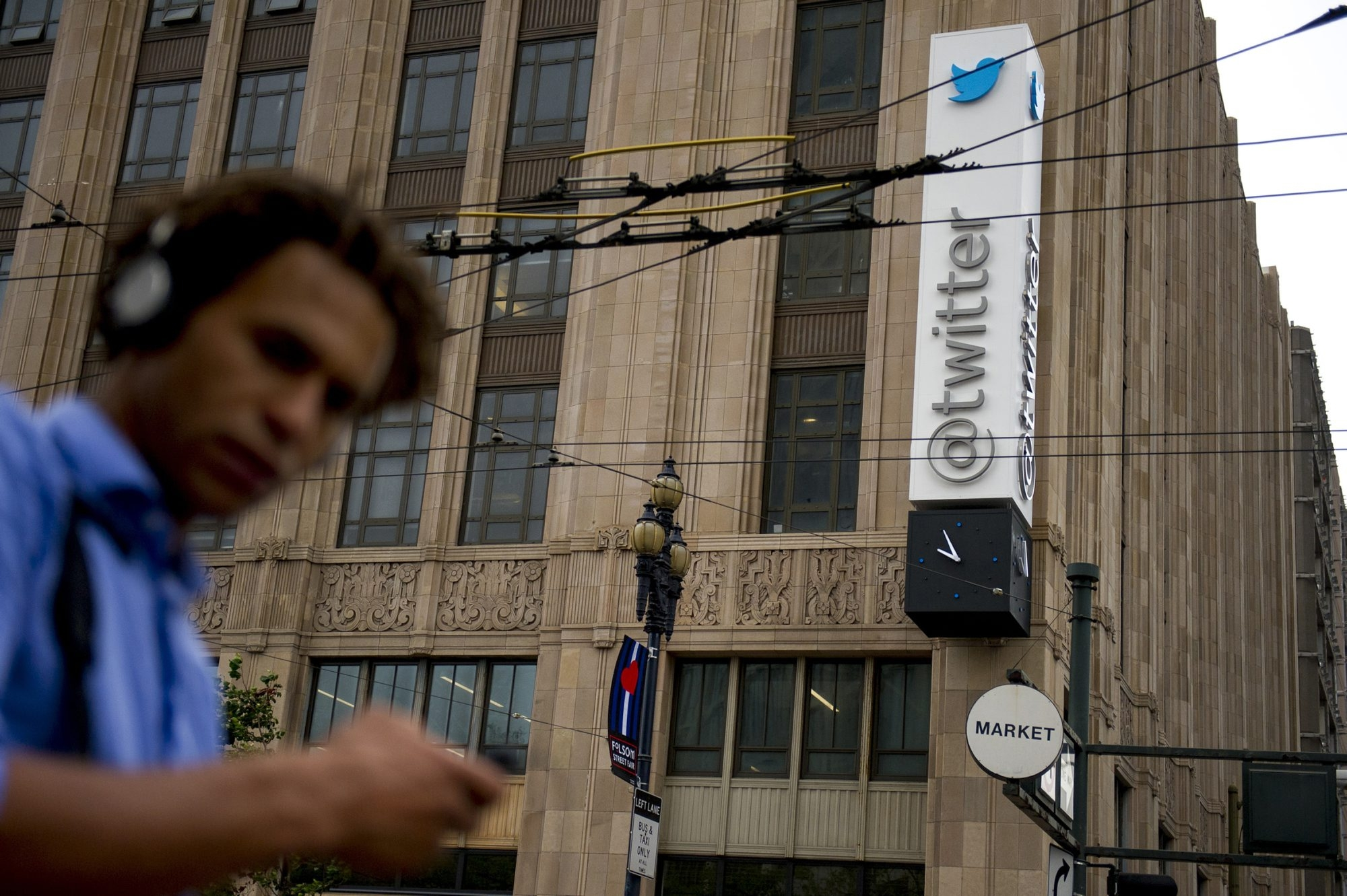 A pedestrian checks his mobile phone in front of Twitter Inc. headquarters in San Francisco, California, U.S., on Friday, Sept. 13, 2013. Twitter Inc.'s market debut will be the most anticipated initial public offering since Facebook Inc. listed last year, and the microblogging service is making sure to avoid some of its rival's pitfalls. Photographer: David Paul Morris/Bloomberg