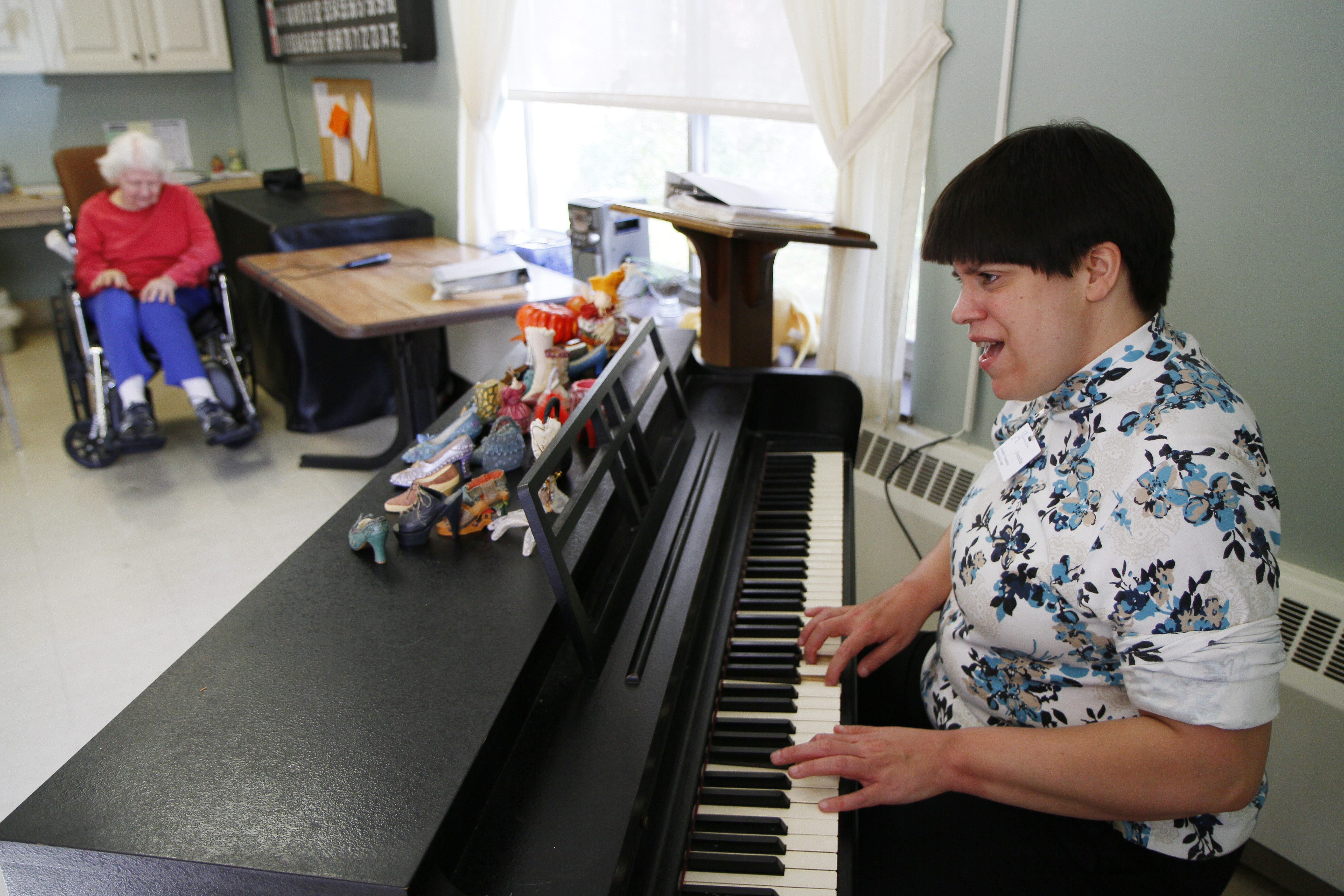 Jenny Trometer, 35, of Wales, performs for residents last week at Absolut Care of Aurora Park in East Aurora. She is legally blind and can't read music, so she learned to play by listening to recordings that her music teacher sent home with her.