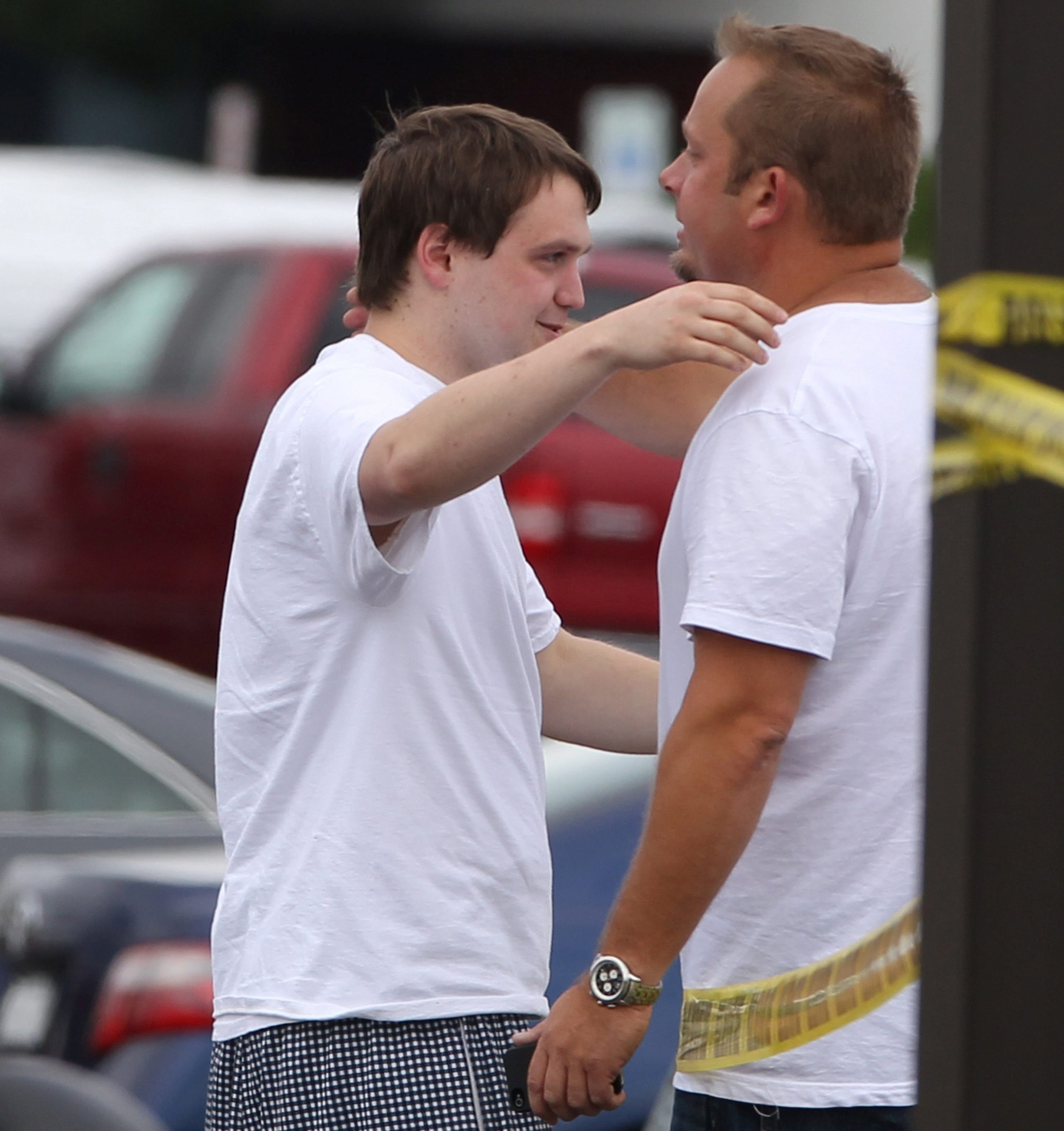 """Bernard """"Bernie"""" Grucza, right, was seen in this file photo about to comfort another man in the death of Laurence C. Wells on June 29 while police gathered information at the crime scene at the Toys 'R' Us in Hamburg."""