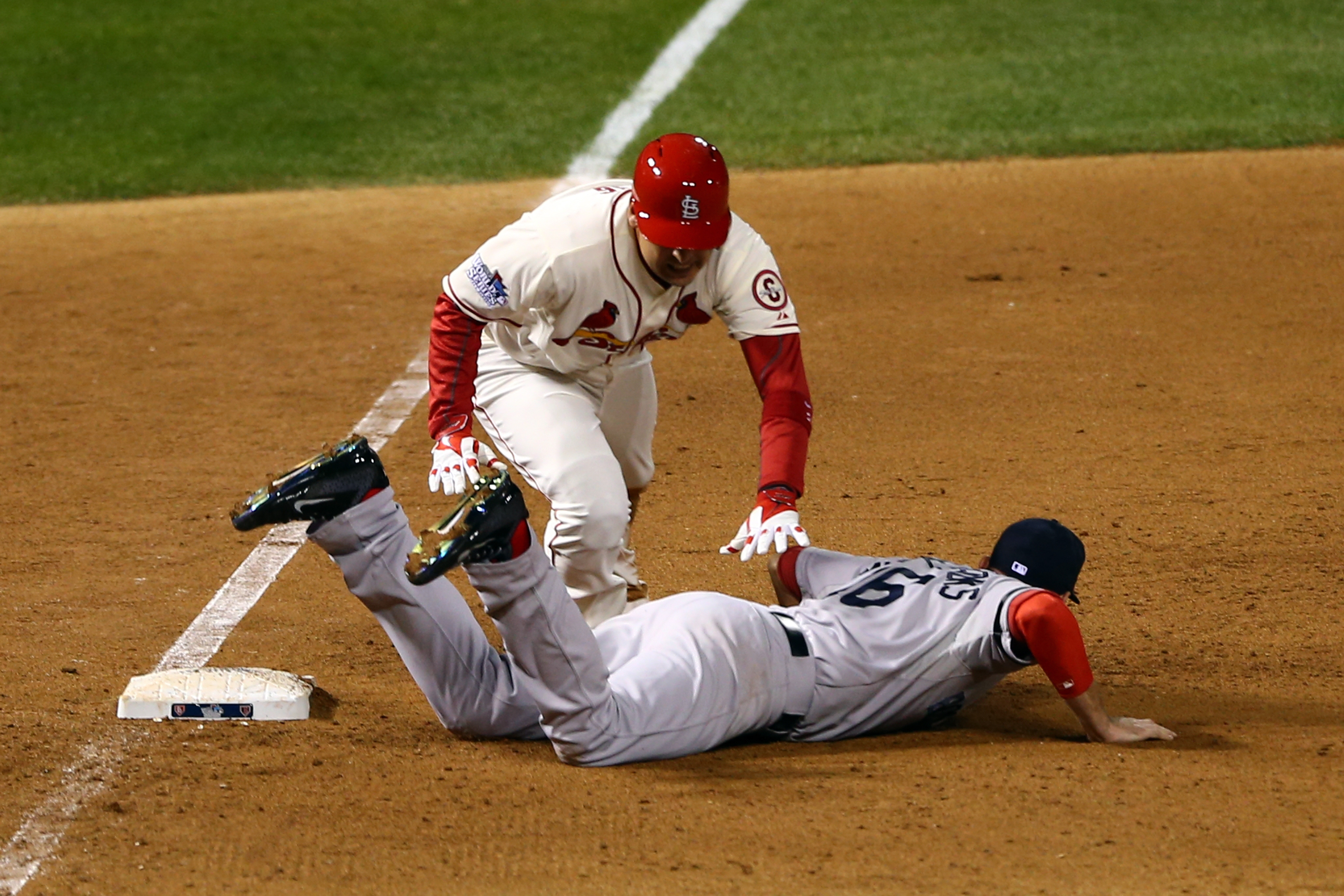 Allen Craig of the Cardinals gets tripped up near third base by Boston's Will Middlebrooks, who was called for obstruction.
