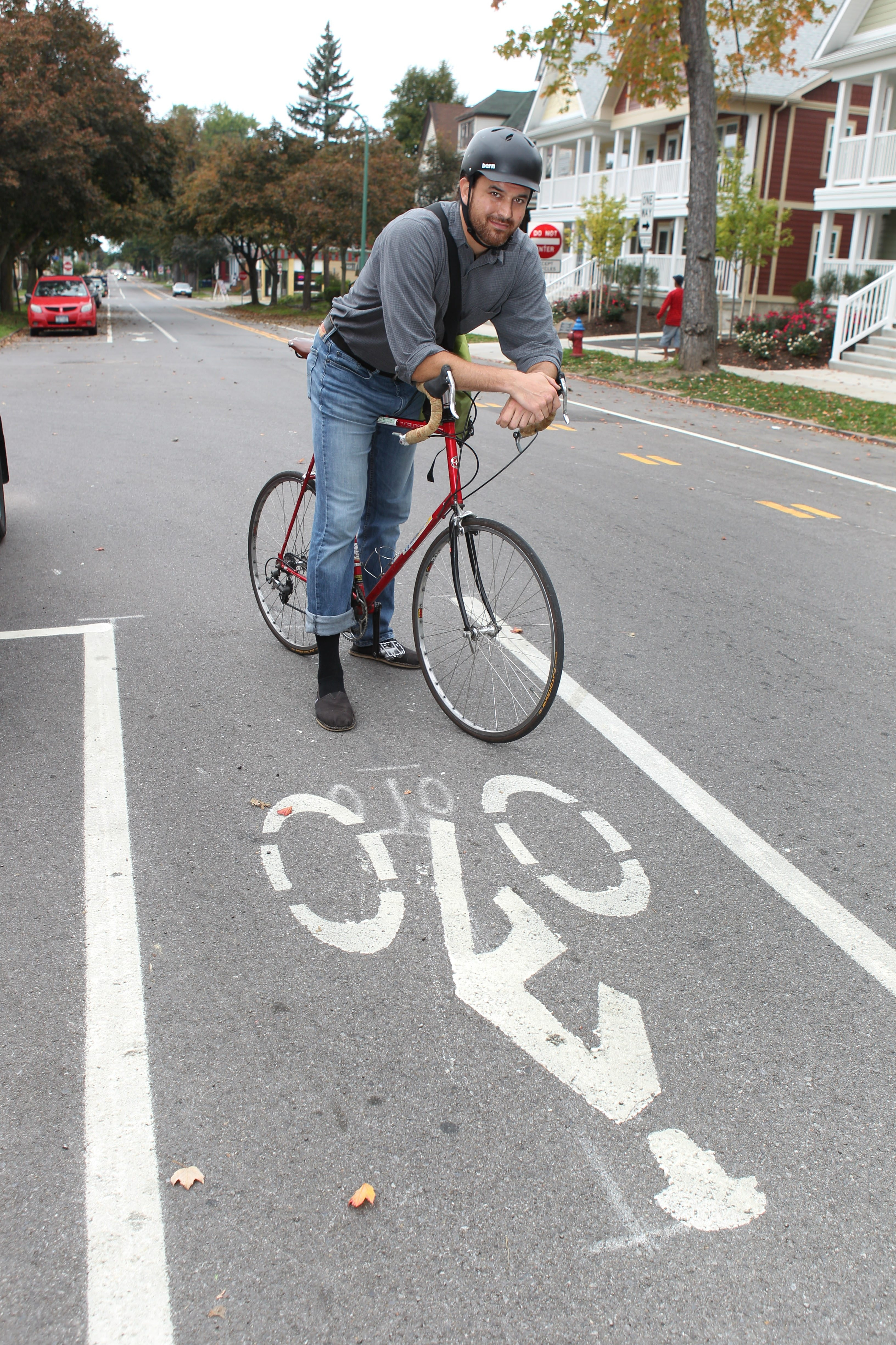 Justin Booth, executive director of GObike Buffalo, rarely uses his car.  He's on one of the new designated biking lanes on Hudson Street.