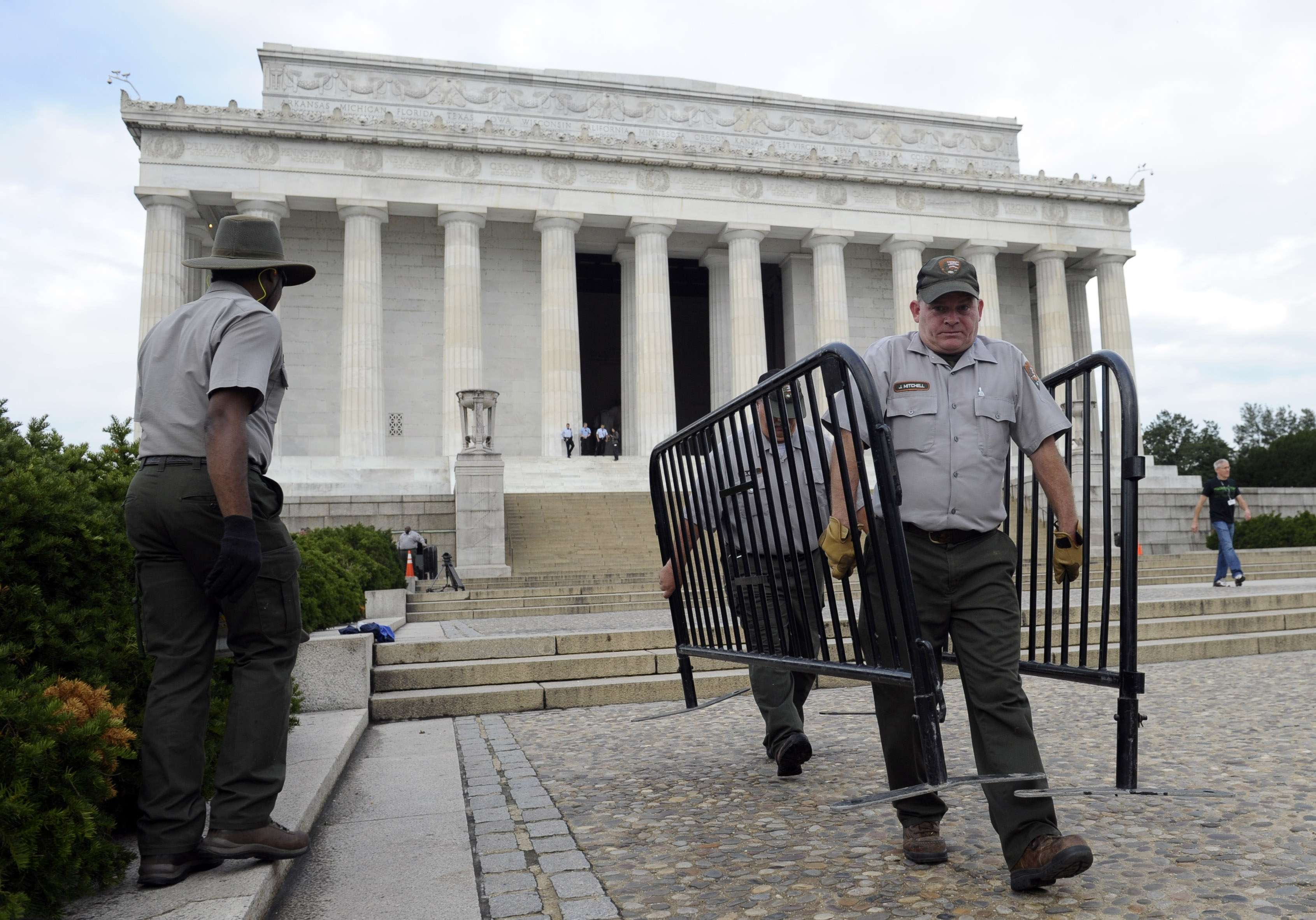 National Park Service employee James Mitchell, right, and others, remove barricades from the grounds of the Lincoln Memorial in Washington today.