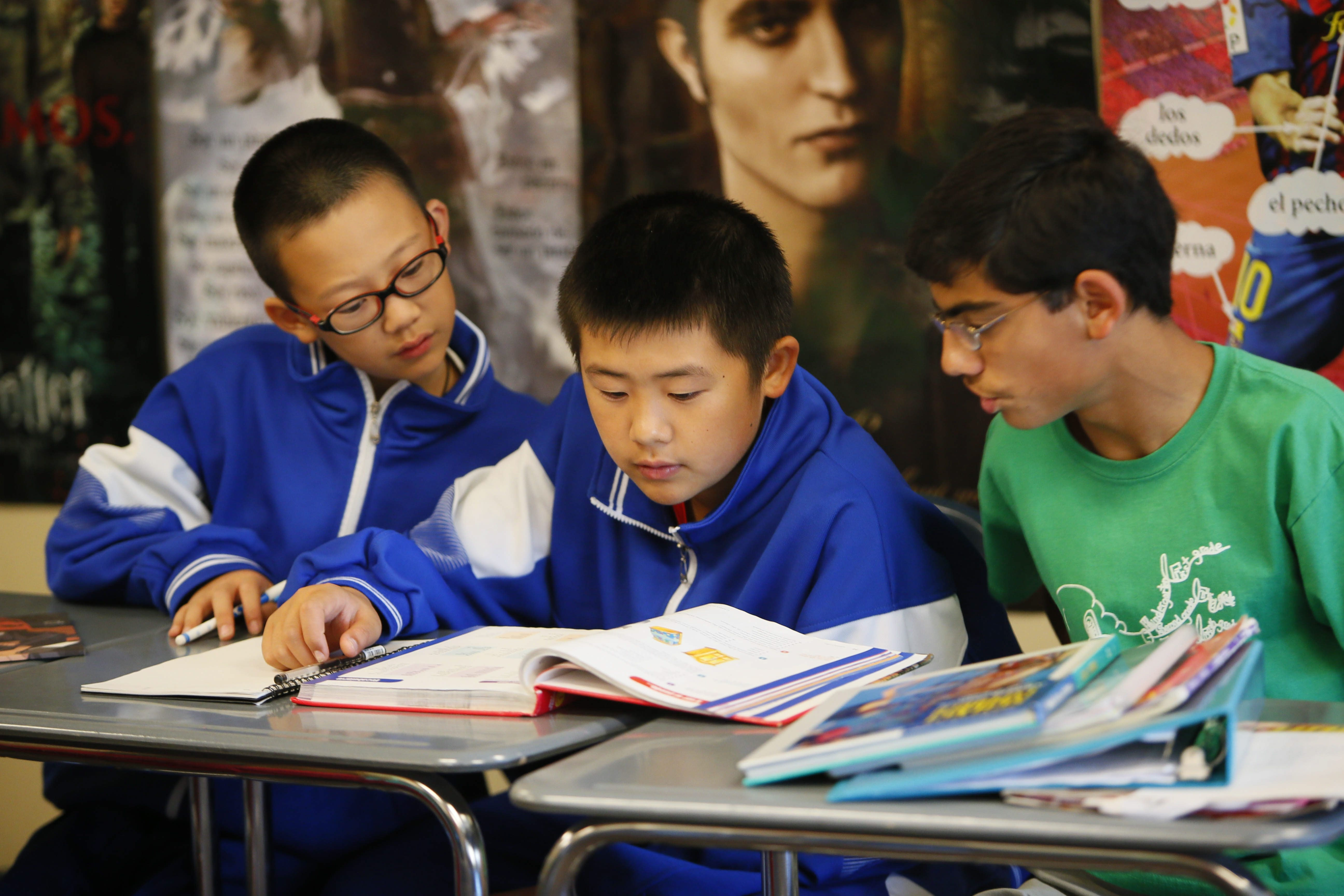 From left, Chinese exchange students Kaixing Wang, left, and Liang Xiao, center, get help from host Tavi Berns as they participate in classes at Lake Shore Middle School in Angola on Thursday.