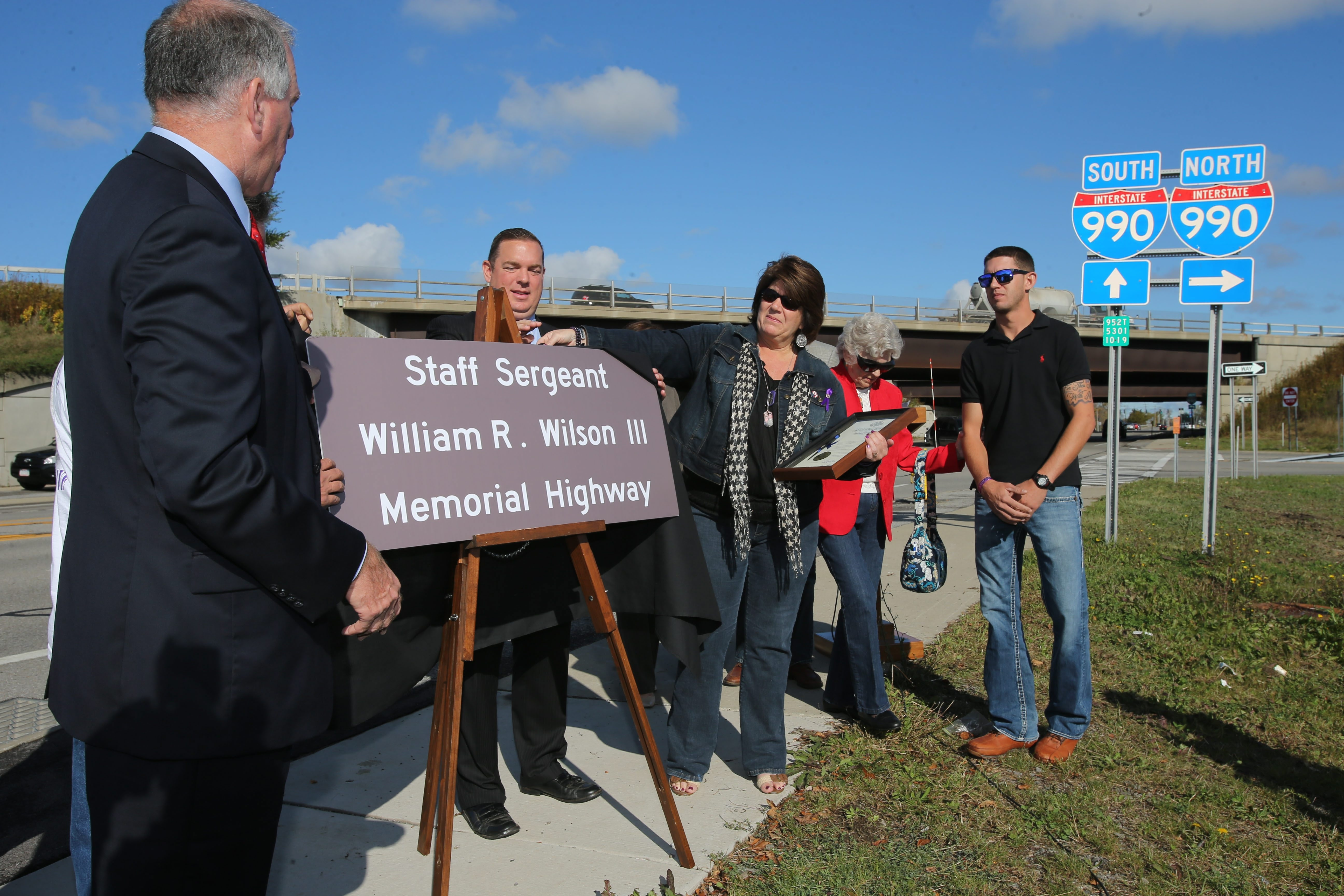 State Sen. Michael H. Ranzenhofer, left, and Kimberly Wilson unveil a sign during a ceremony to rename most of the Lockport Expressway as Staff Sgt. William R. Wilson III Memorial Highway, in honor of her late son Monday. Her son Jeremy Wilson, right, looks on.