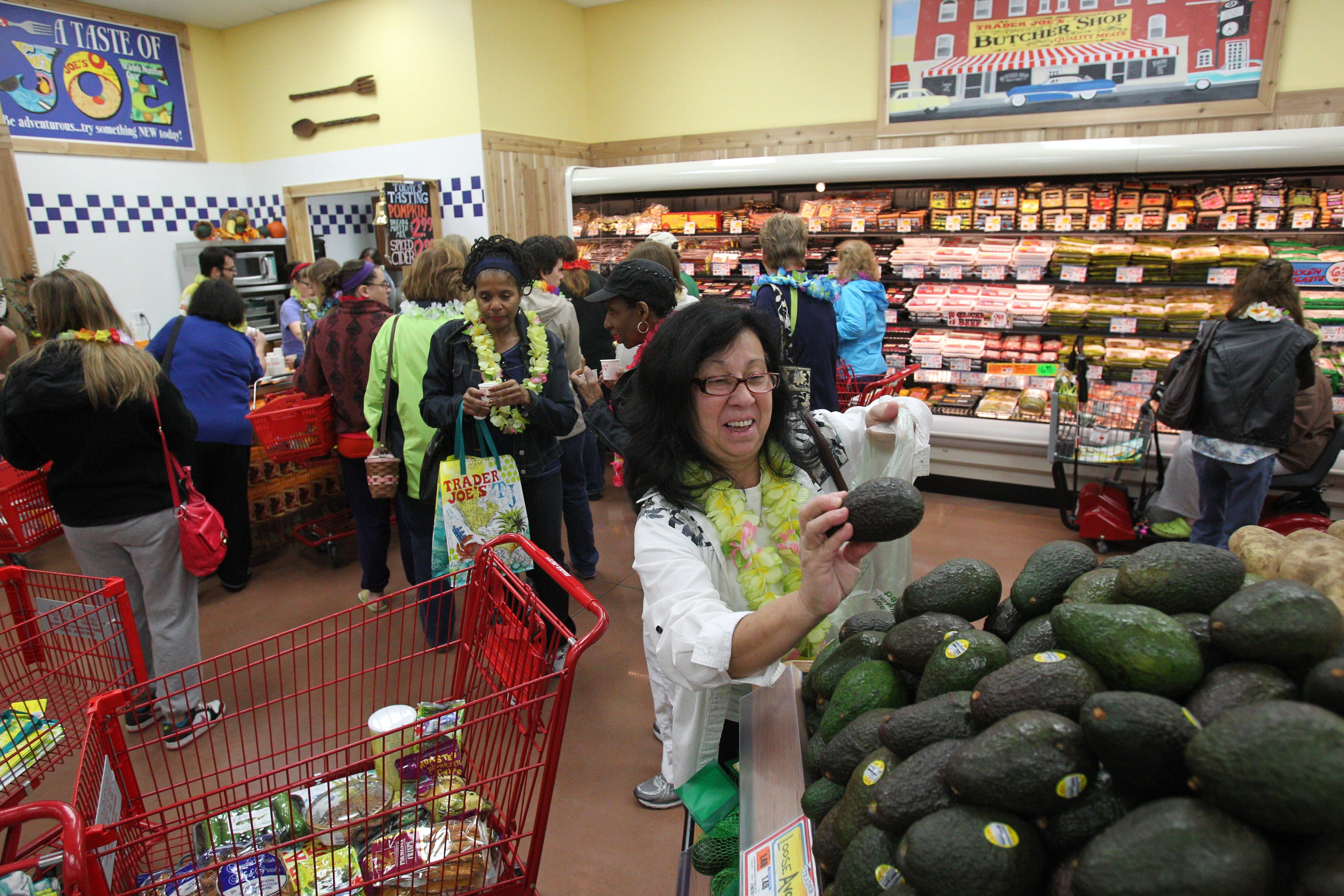 Kathy Weixlmann, top, of Niagara Falls picks out avocados at the opening of Trader Joe's Friday. She visited the chain's store in other cities and knew where to turn. The opening featured an outside performance by the Caribbean Extravaganza. Shoppers also were greeted with a lei and a shopping bag.