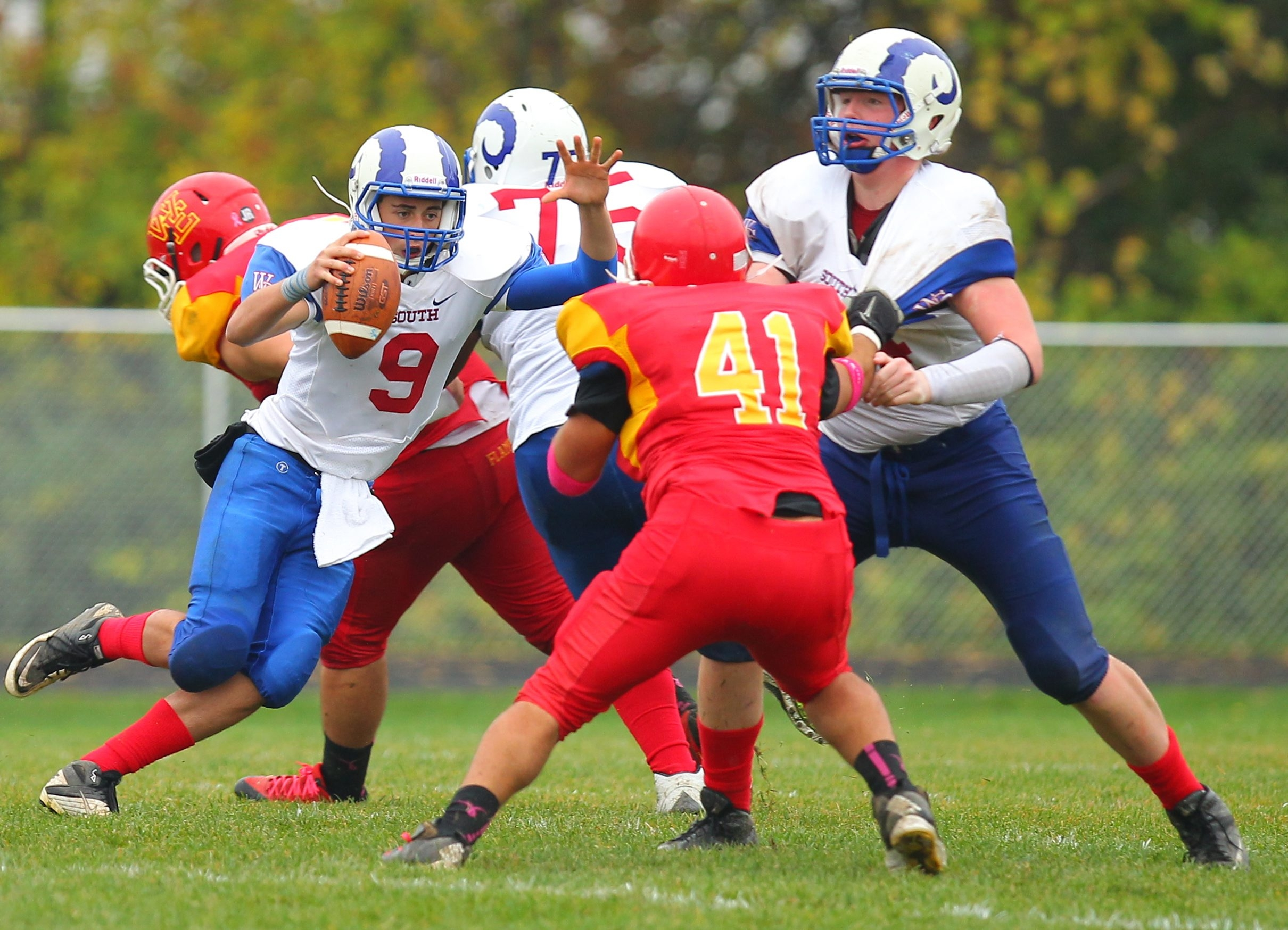 Williamsville South's Sam Castronova (9) tries to escape a collapsing pocket as Williamsville East's Mike Losi (41) closes in during South's 28-7 victory.