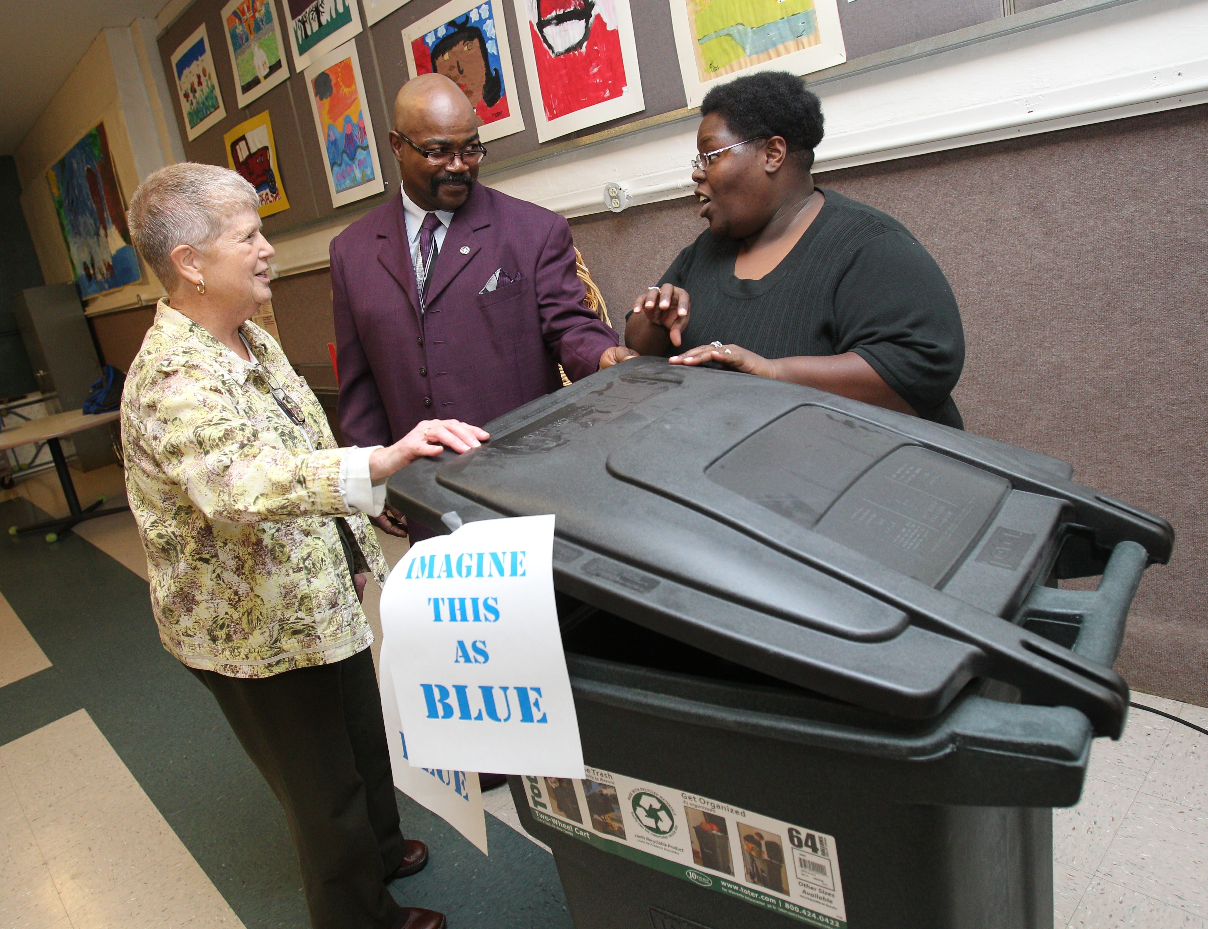 Sister Beth Brosmer, left, president of Niagara Organizing Alliance for Hope, speaks with Tyrone Wooten and Sammantha Hollis about the need for garbage totes Sunday in Niagara Falls.