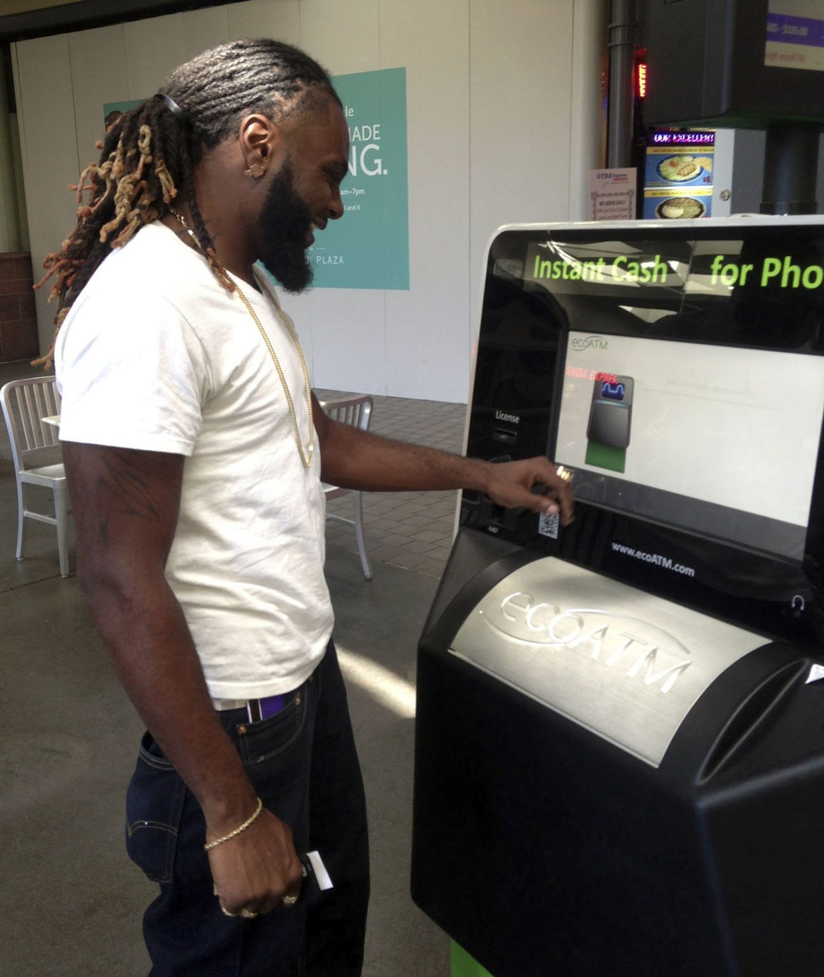 Marcellus Lang, a security guard at a sports bar in Sacramento, Calif., uses an ecoATM kiosk at a mall to exchange a used cellphone and an old iPod Touch for $59 in cash.