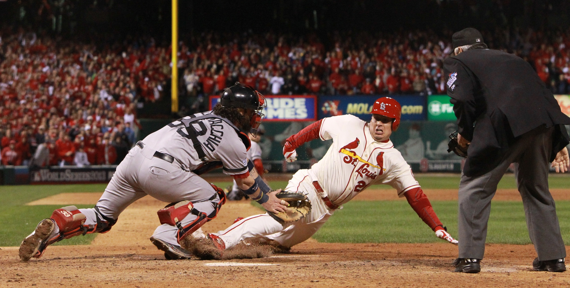 The Cardinals' Allen Craig is tagged by Boston Red Sox catcher Jared Saltalamacchia but he is ruled safe with the game-winning run due to interference when he tried to leave third base in the ninth inning during Game Three on Saturday night.