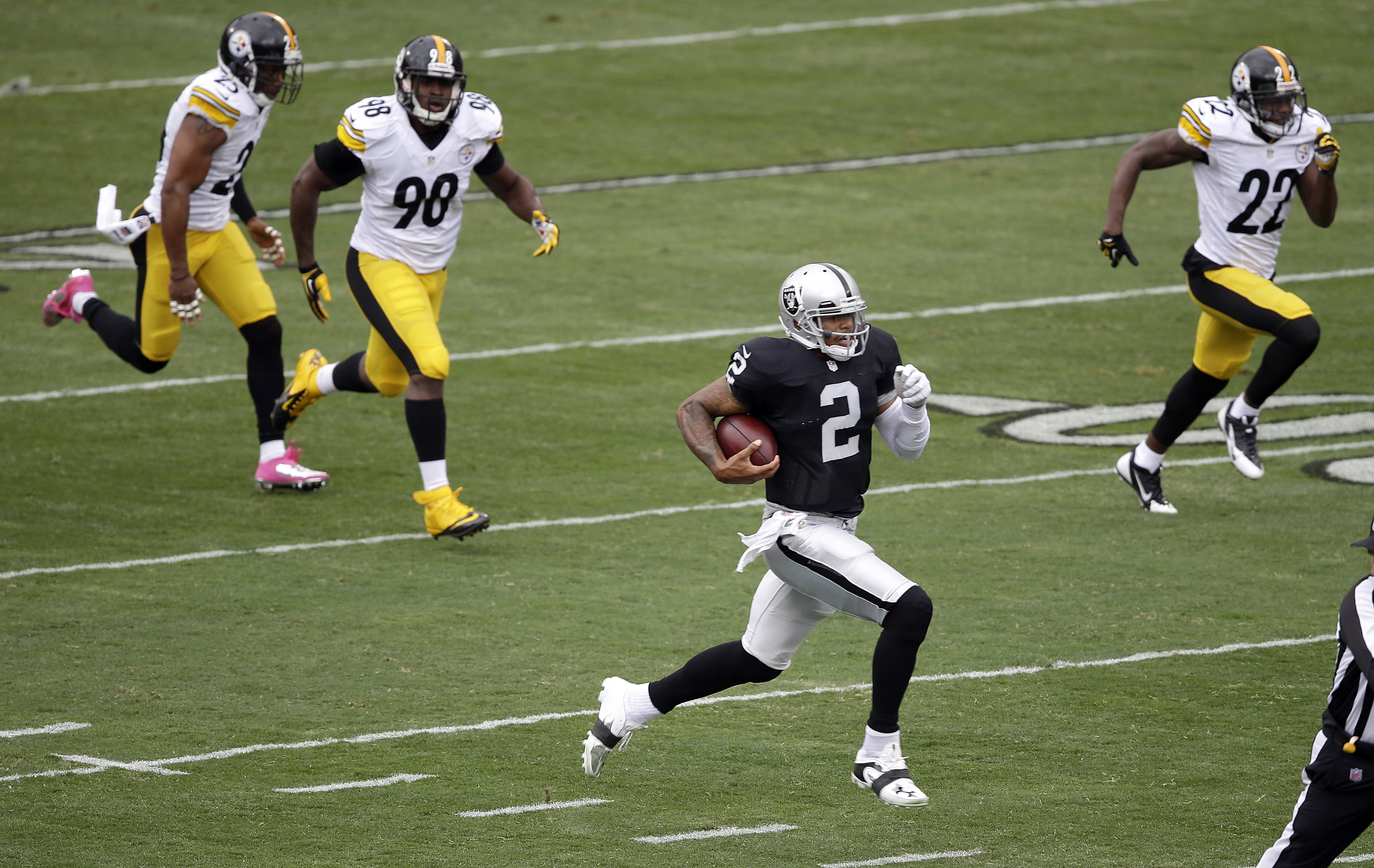 Oakland's Terrelle Pryor pulls away from Pittsburgh Steelers linebacker Vince Williams, left, and cornerback William Gay on his way to a 93-yard touchdown, the longest TD run ever by an NFL quarterback.
