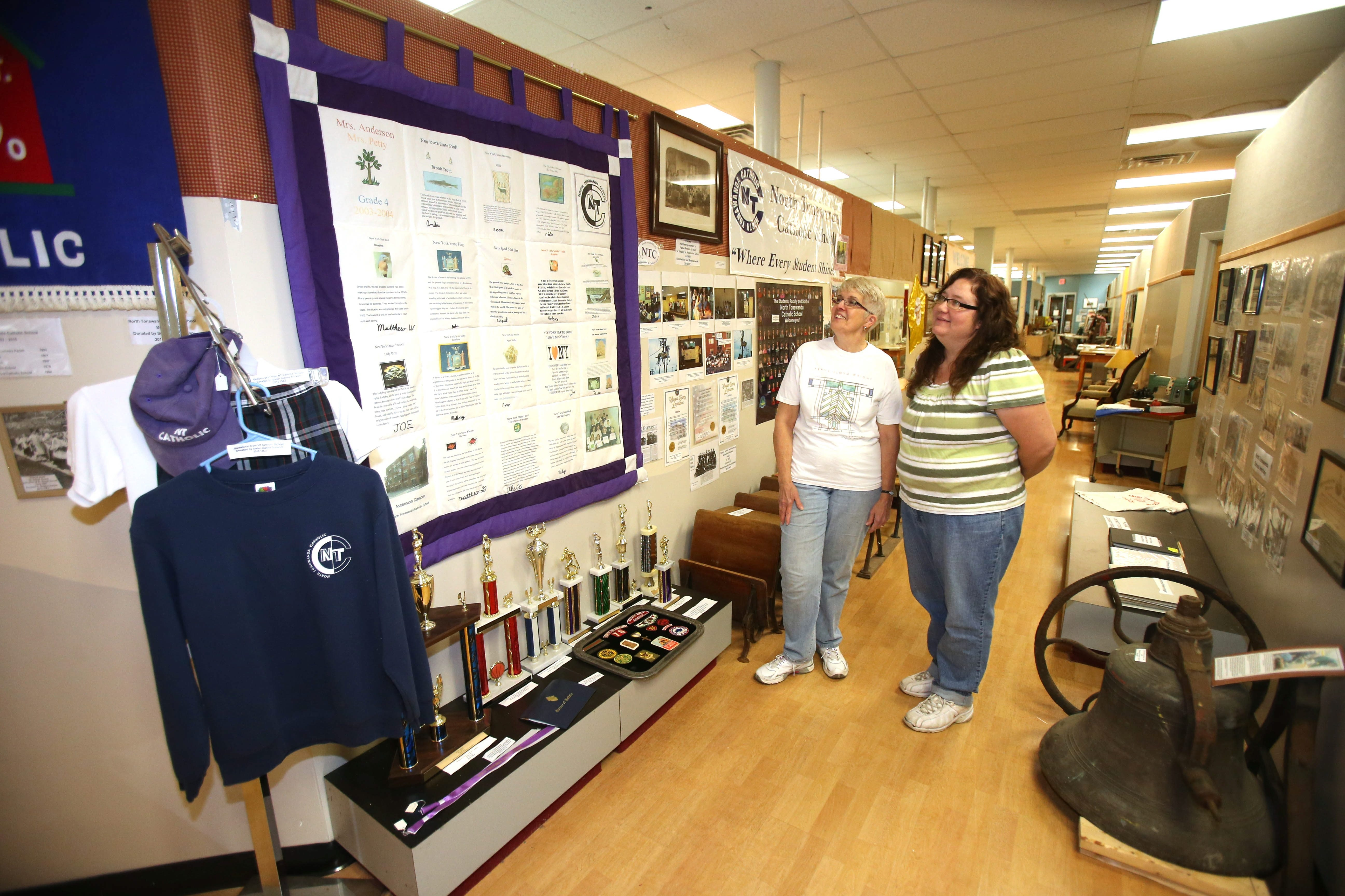 Volunteers Marg Bauza, left, and Penny Buterbaugh-Naimi admire the new dedicated display of North Tonawanda schools they just finished at the Webster Street museum.