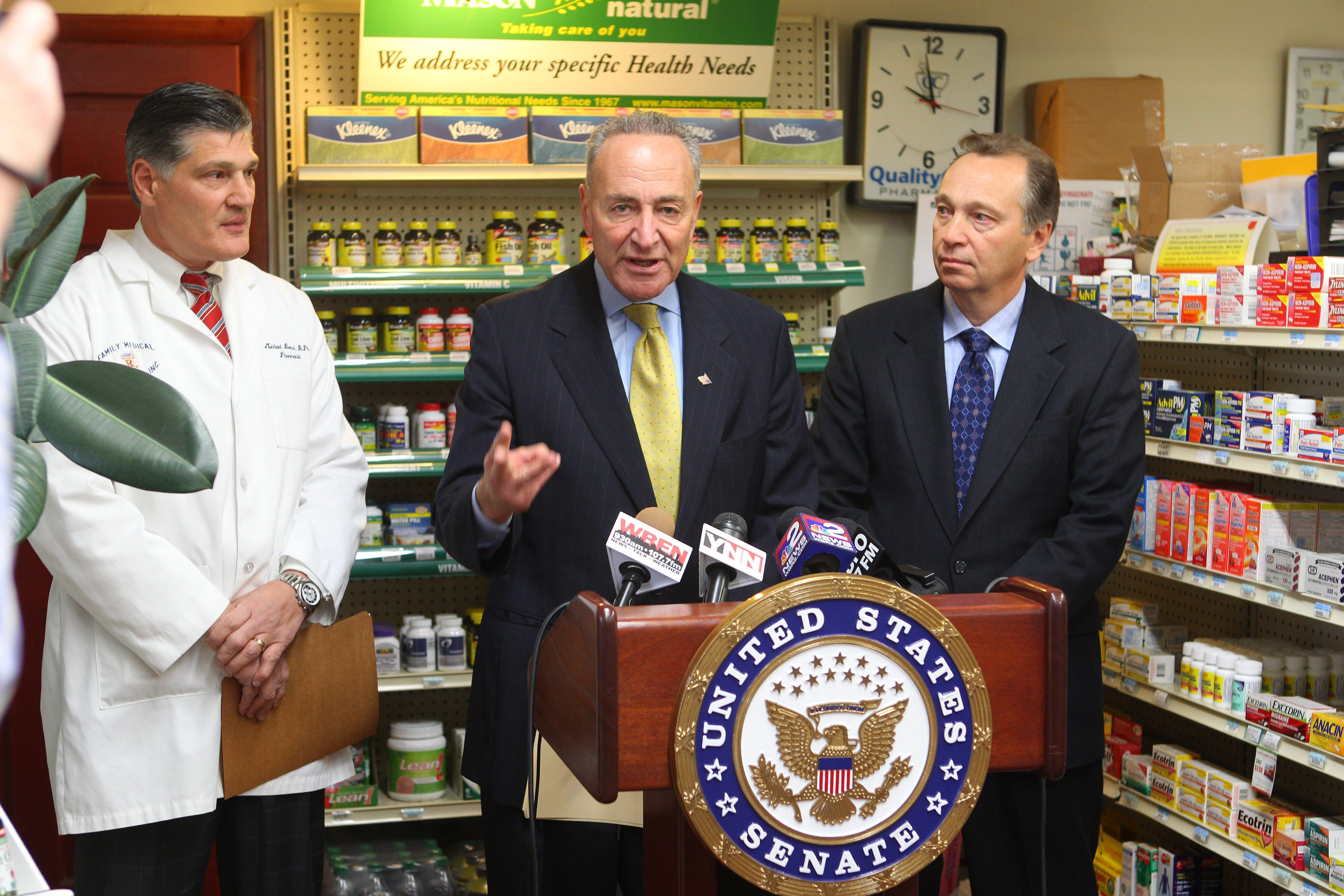Sen. Charles E. Schumer with pharmacists Michael Rossi, left, and Dennis Galluzzo, right, at a news conference in Family Medical Pharmacy in Amherst.