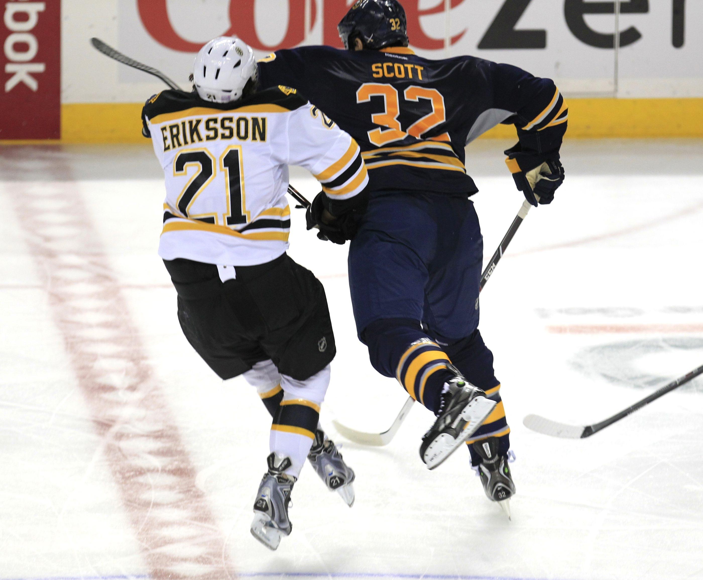 Buffalo Sabre John Scott (32) checks Boston Bruin Loui Eriksson (21)  during third period action  at the First Niagara Center Wednesday. (Harry Scull Jr./Buffalo News)