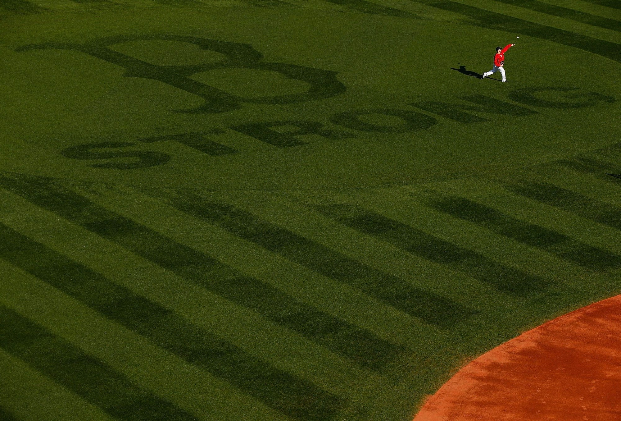 """Daniel Nava of the Red Sox works out in center field, where the Boston Strong logo with the giant Red Sox """"B"""" is mowed into the grass. Game One of the World Series is tonight between the Red Sox and the Cardinals."""