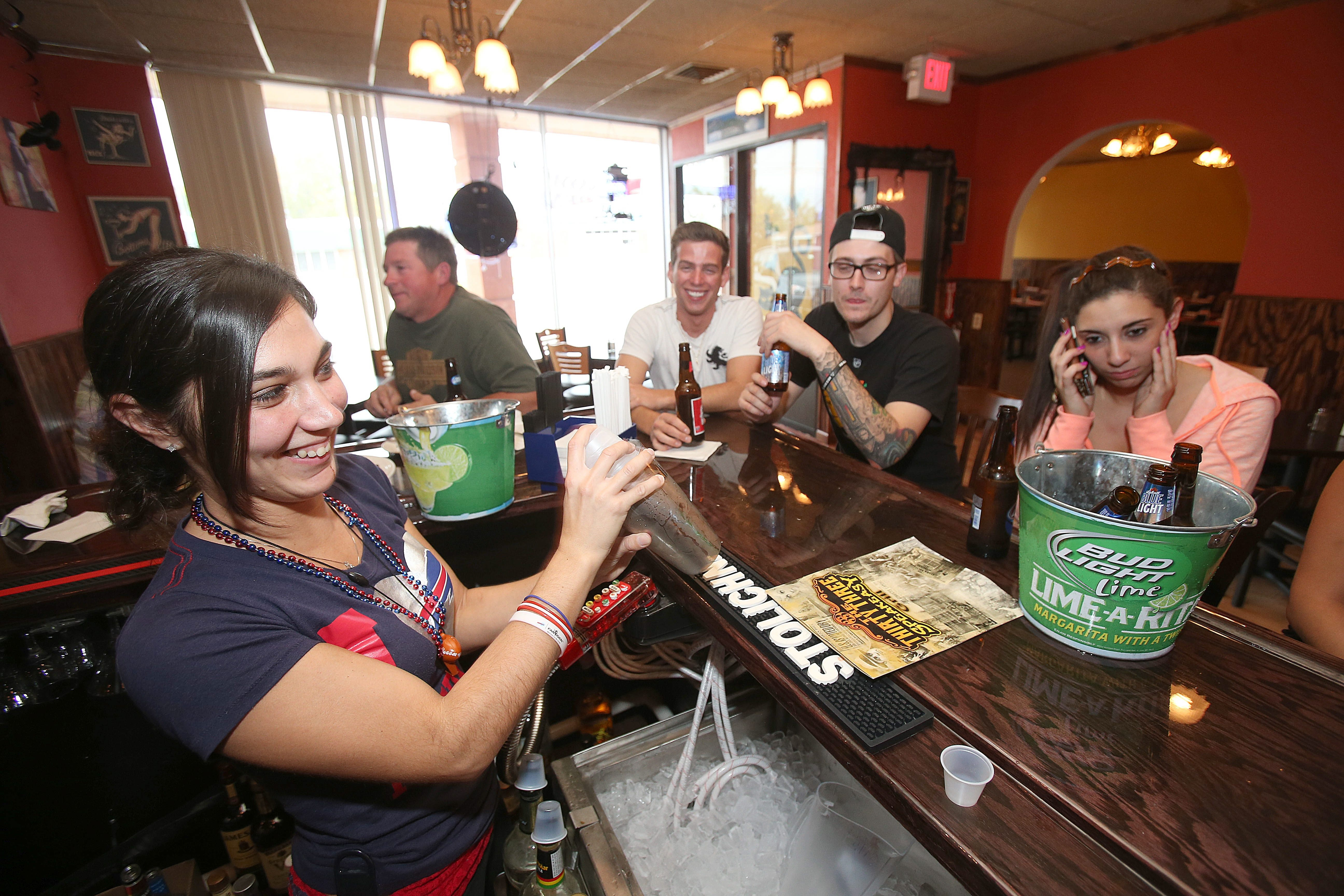 Bartender/Manager Holly Monin shakes up a drink and keeps the patrons happy during the Bills game Sunday at Thirty Three Speakeasy Grill in Cheektowaga.