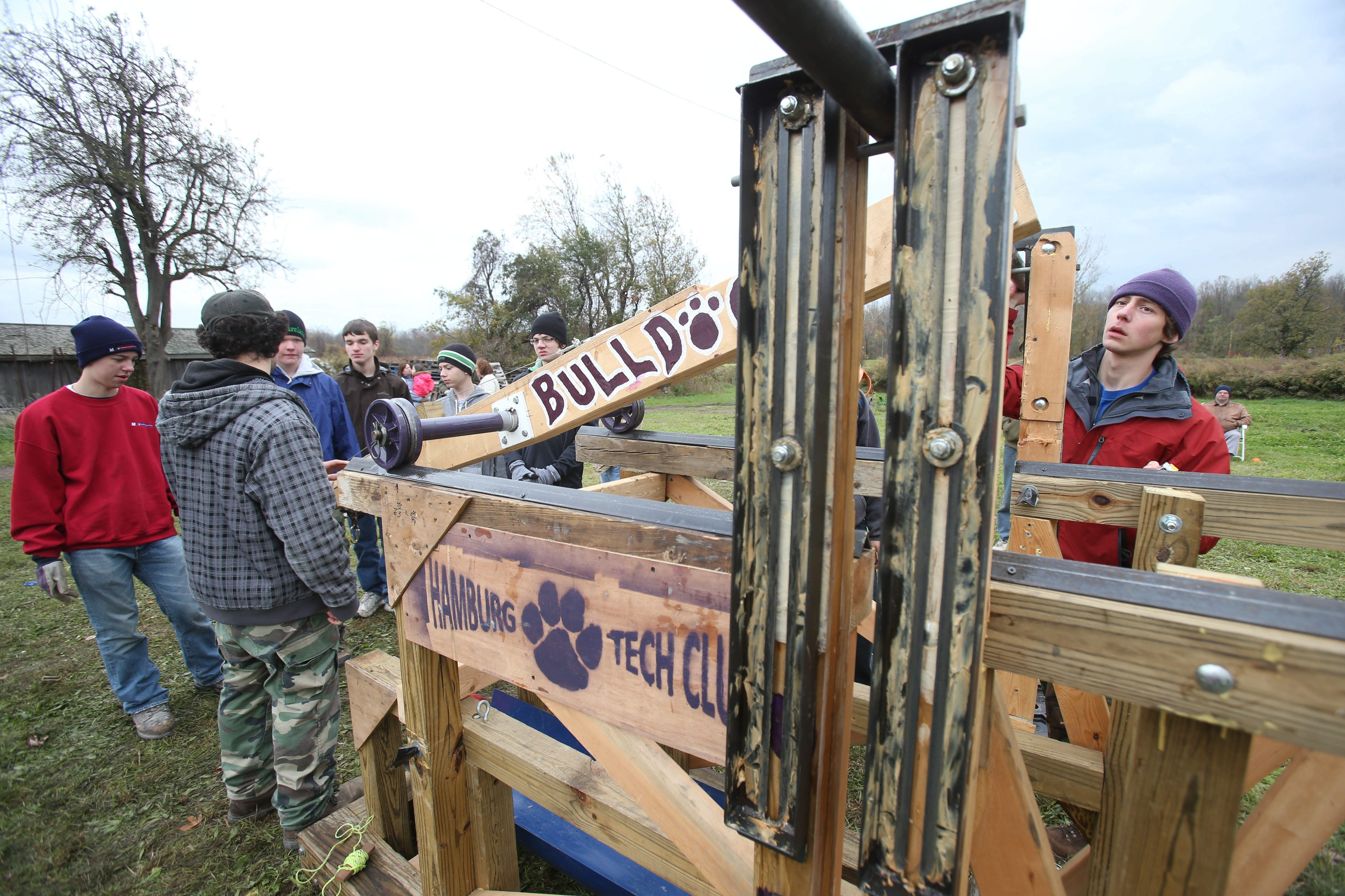 Members of the Hamburg High School tech club, including team captain Kevin Gonser, right, assemble their trebuchet for the pumpkin-flinging contest at the Great Pumpkin Farm in Clarence on Sunday. The team won the target competition.