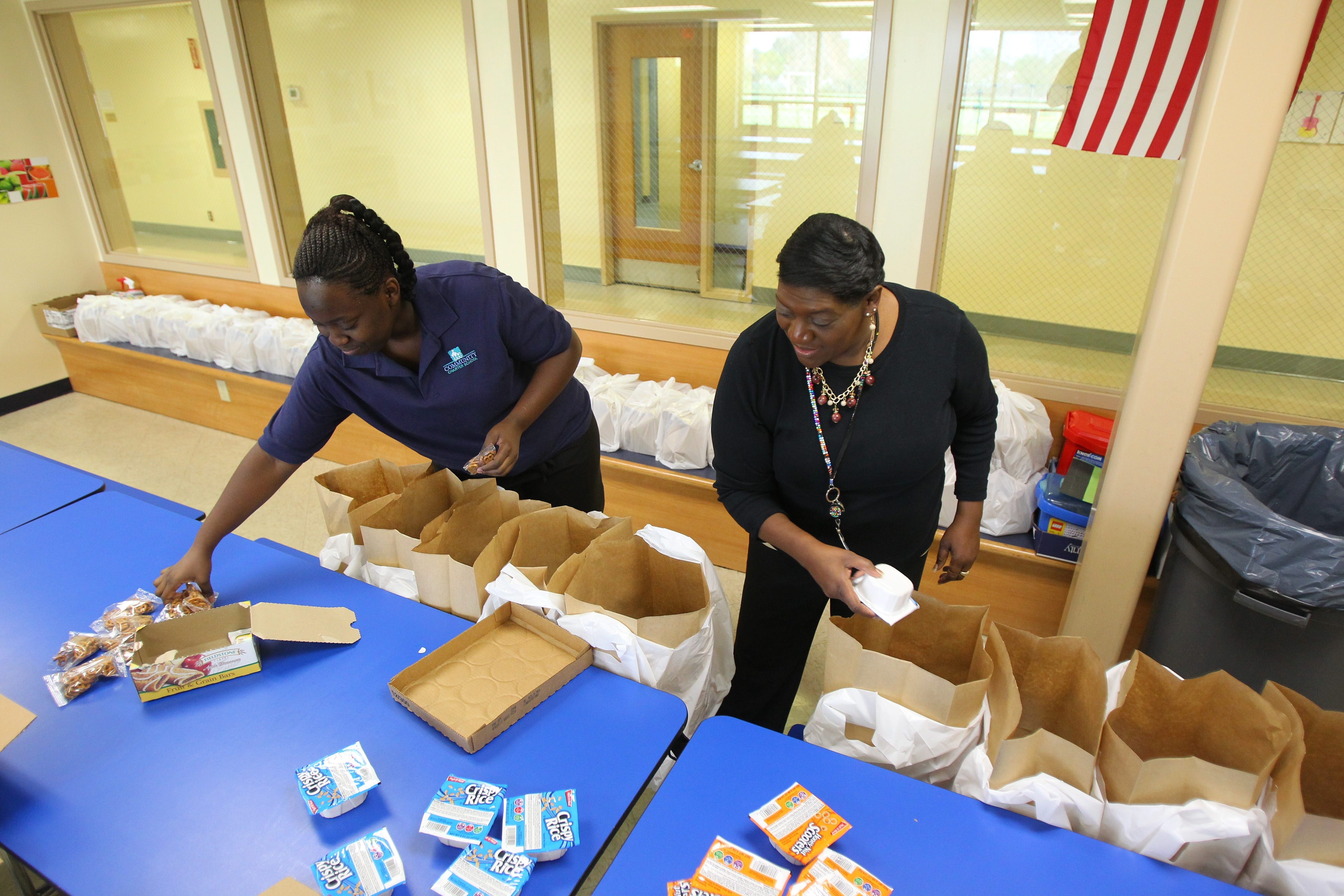Community Charter School head cook Teri Gamble, right, and cafeteria staffer Joniesha Eldridge fill bags of food for needy children at the school to take home for the weekend. They were in the school cafeteria in Buffalo on Thursday.