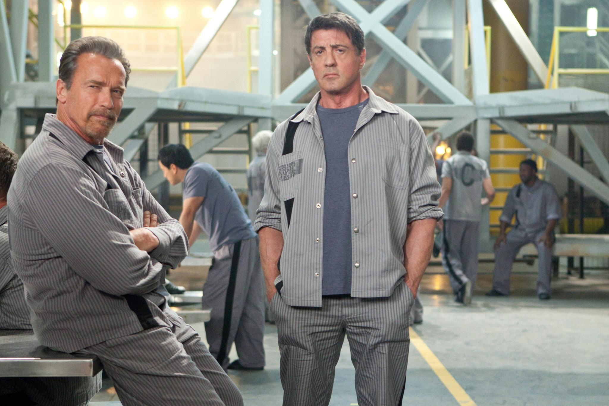 "Arnold Schwarzenegger, left, and Sylvester Stallone play inmates trying to break out in ""Escape Plan."""
