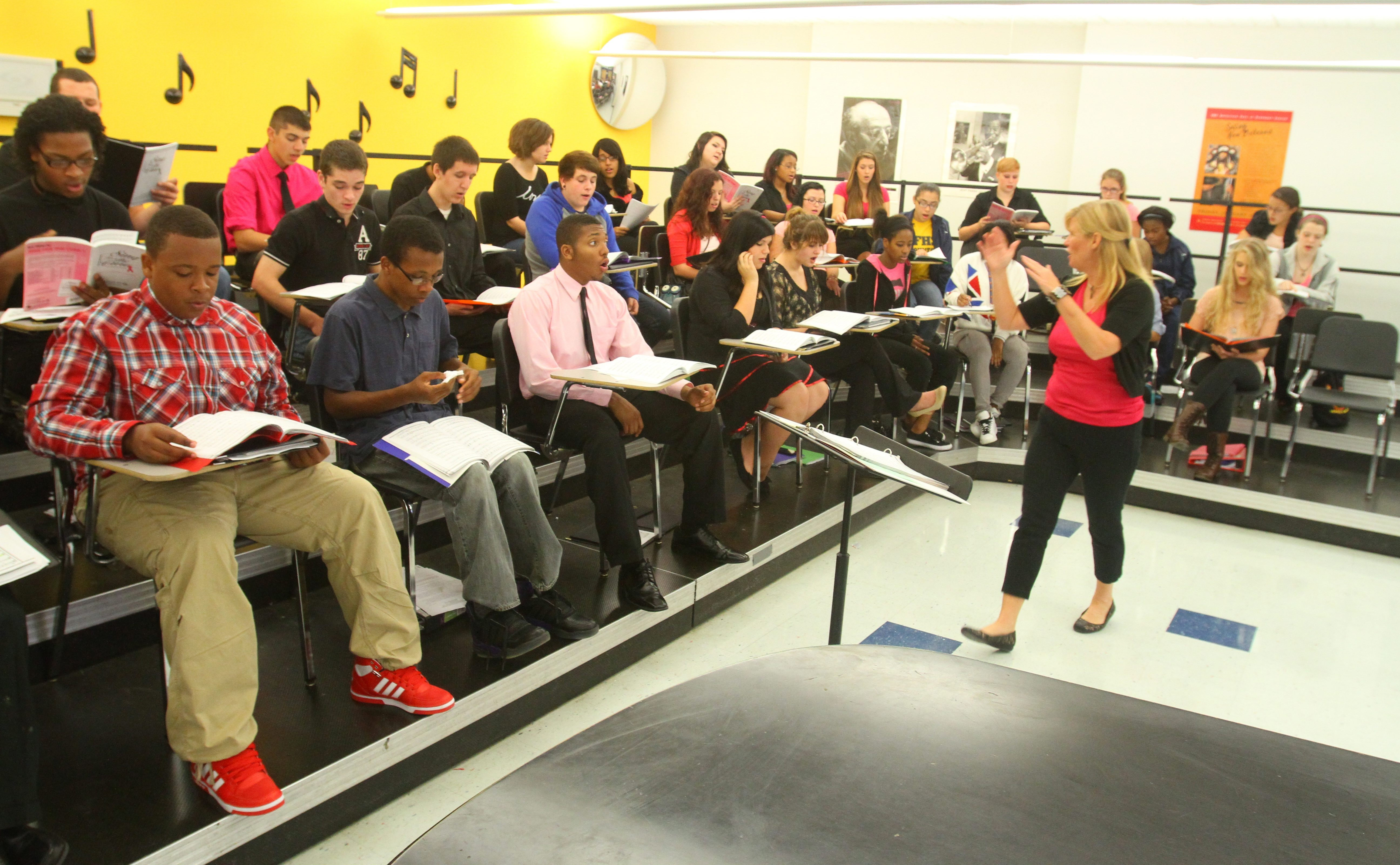 Linda Werder, choir director at Niagara Falls High School, prepares students for Wednesday evening's concert to raise funds for Breast Cancer Network of WNY. Claudia Andres is doing the same at Wilson for Thursday performance there.